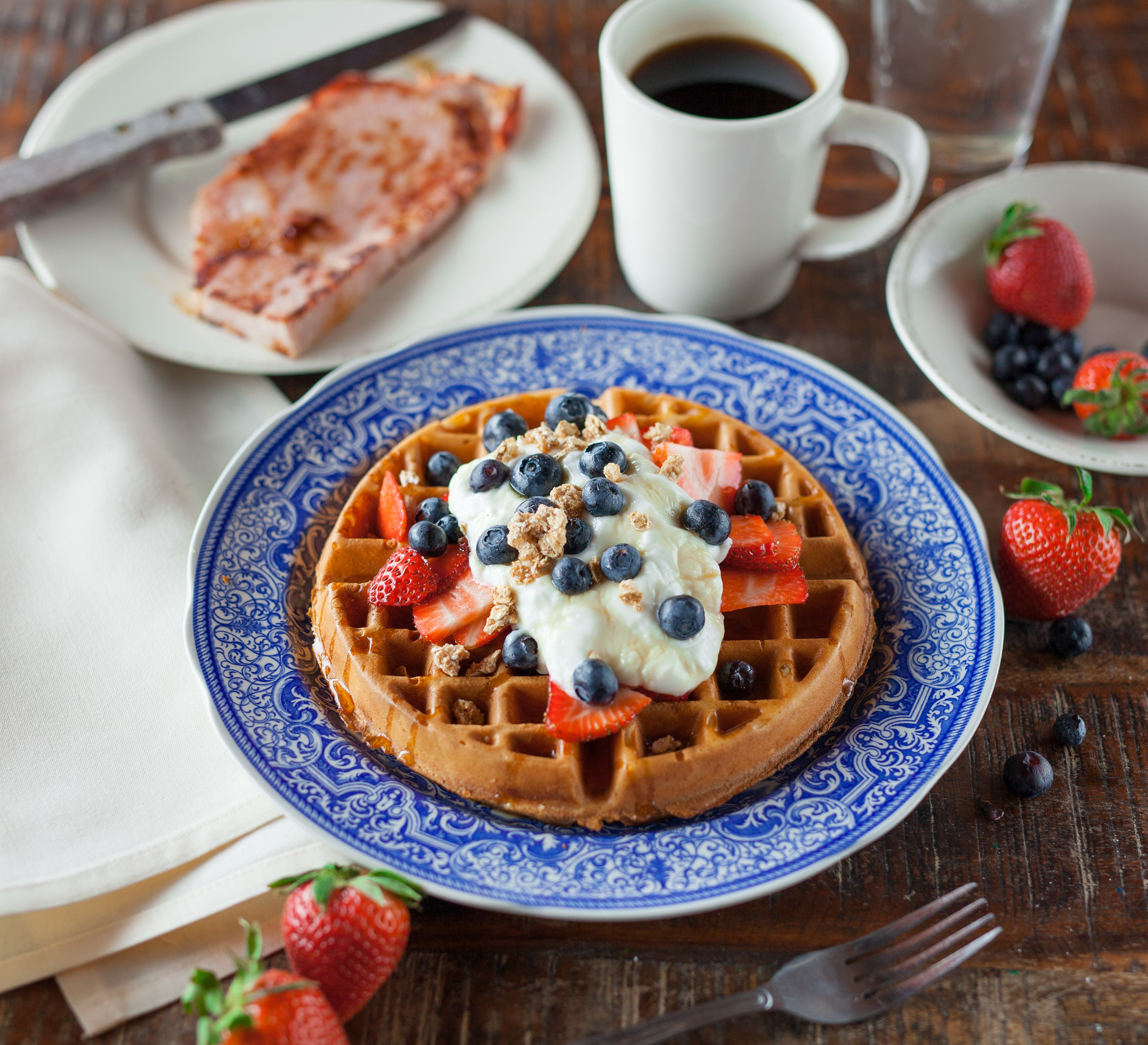 Round waffles with whipped cream, strawberries and blueberries next to a cup of coffee