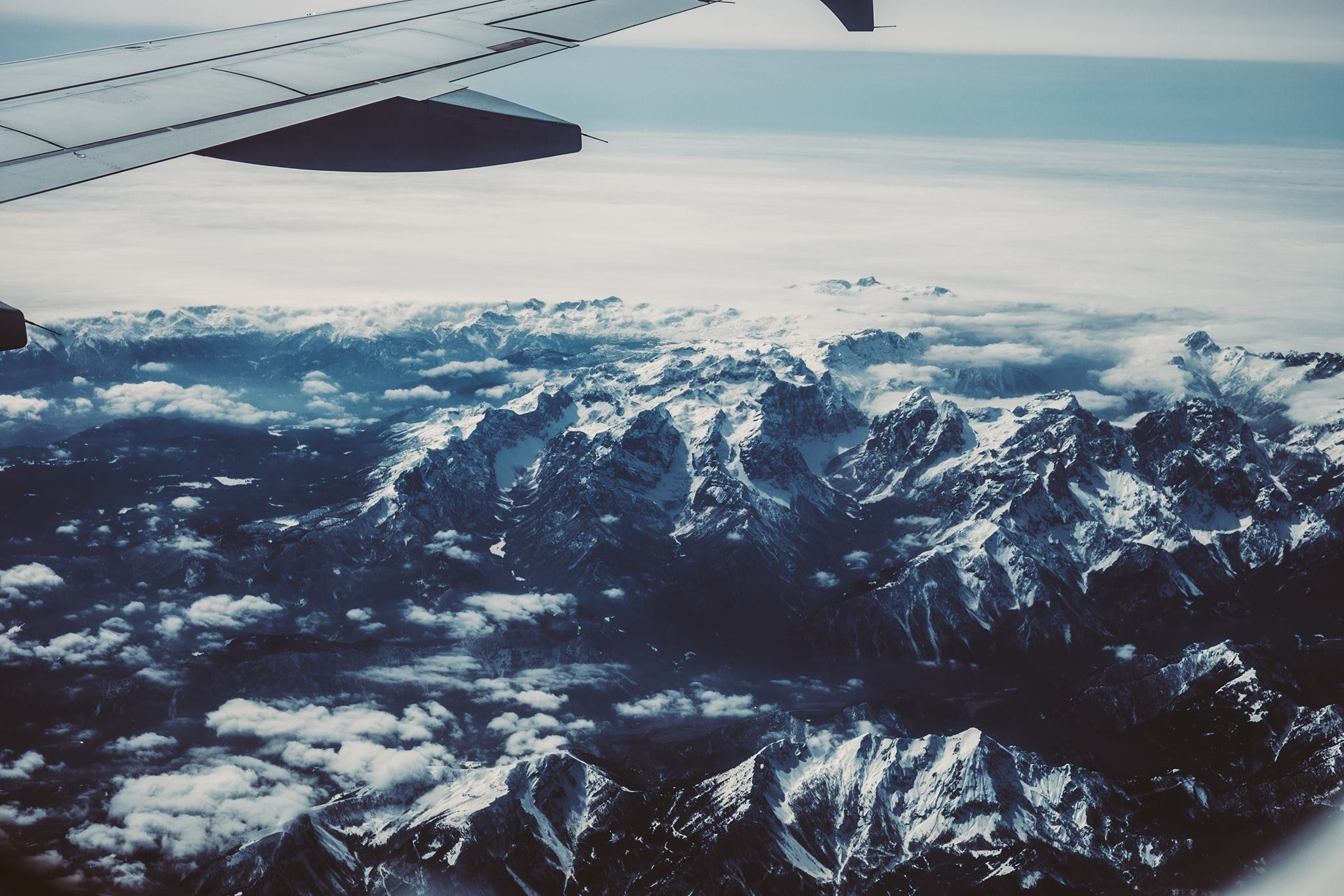 View of airplane wing crossing snowy mountains