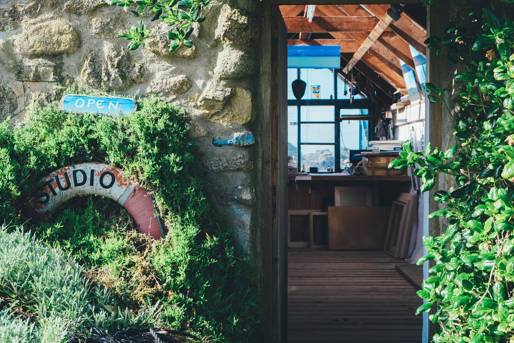 Shot of daytime studio through the doorway with lifesaver and plants on wall, Isles of Scilly