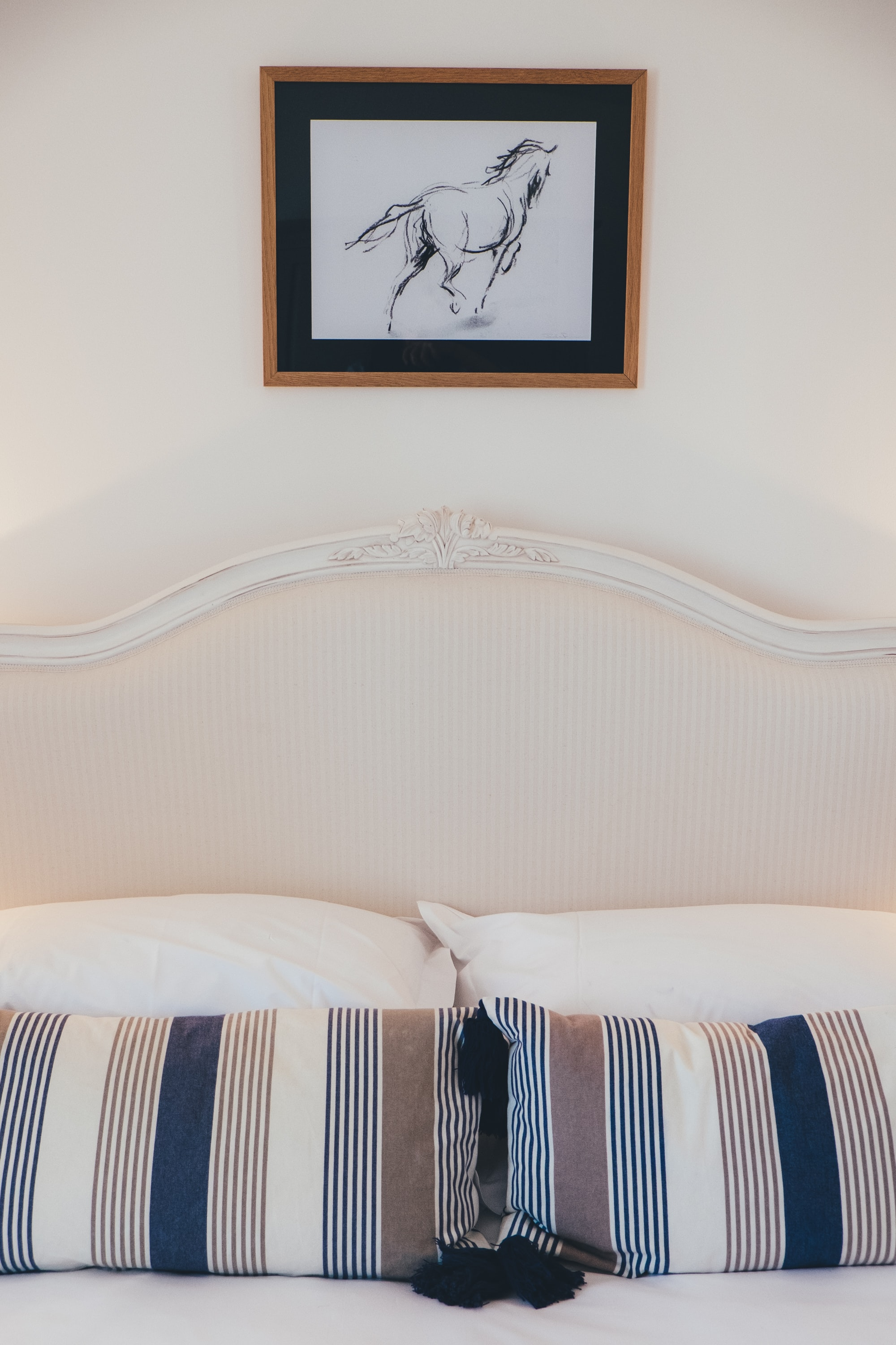 A framed sketch of a running horse hangs on the wall above a double bed