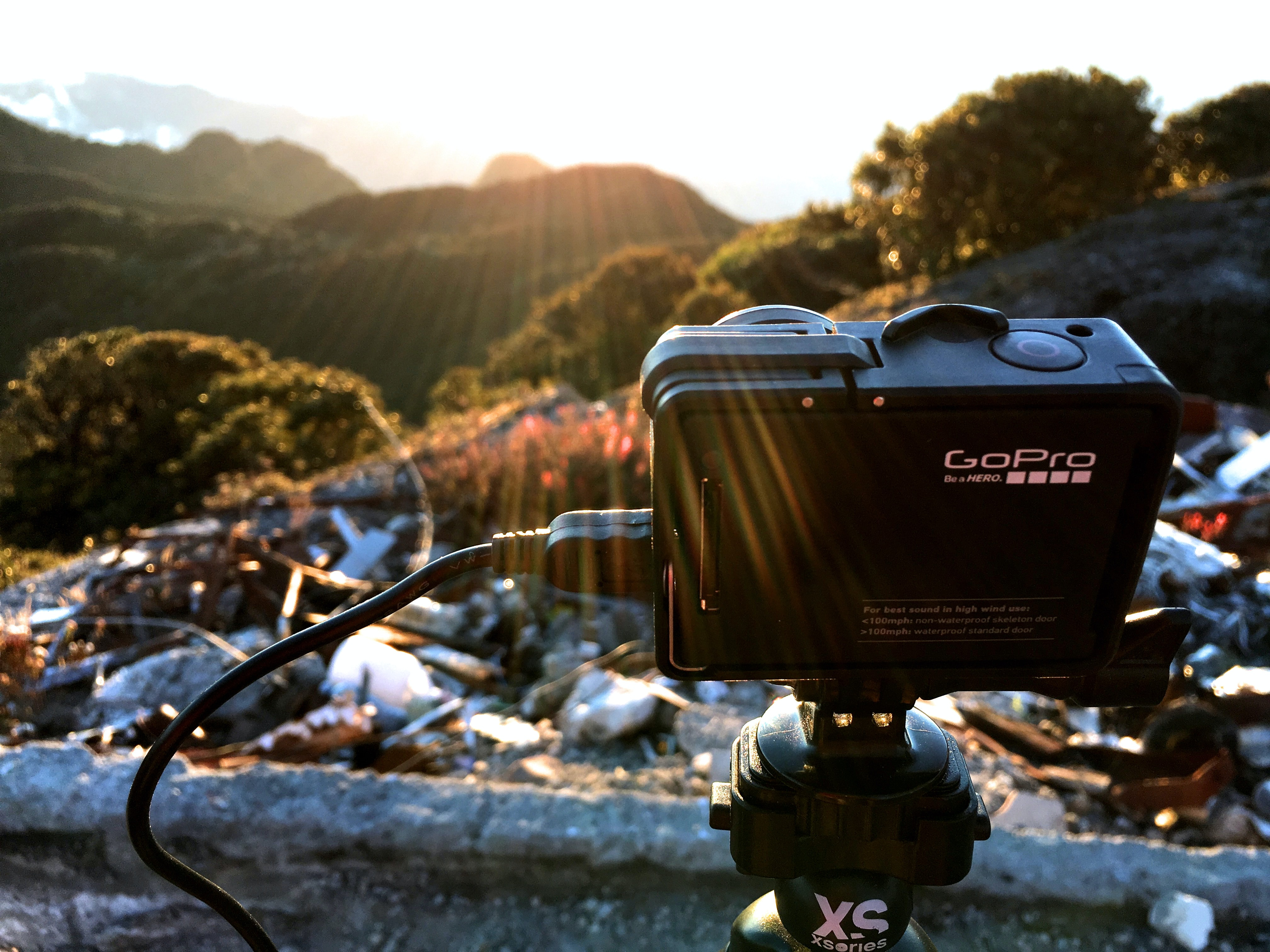 A GoPro camera set up on a tripod in a mountain area.