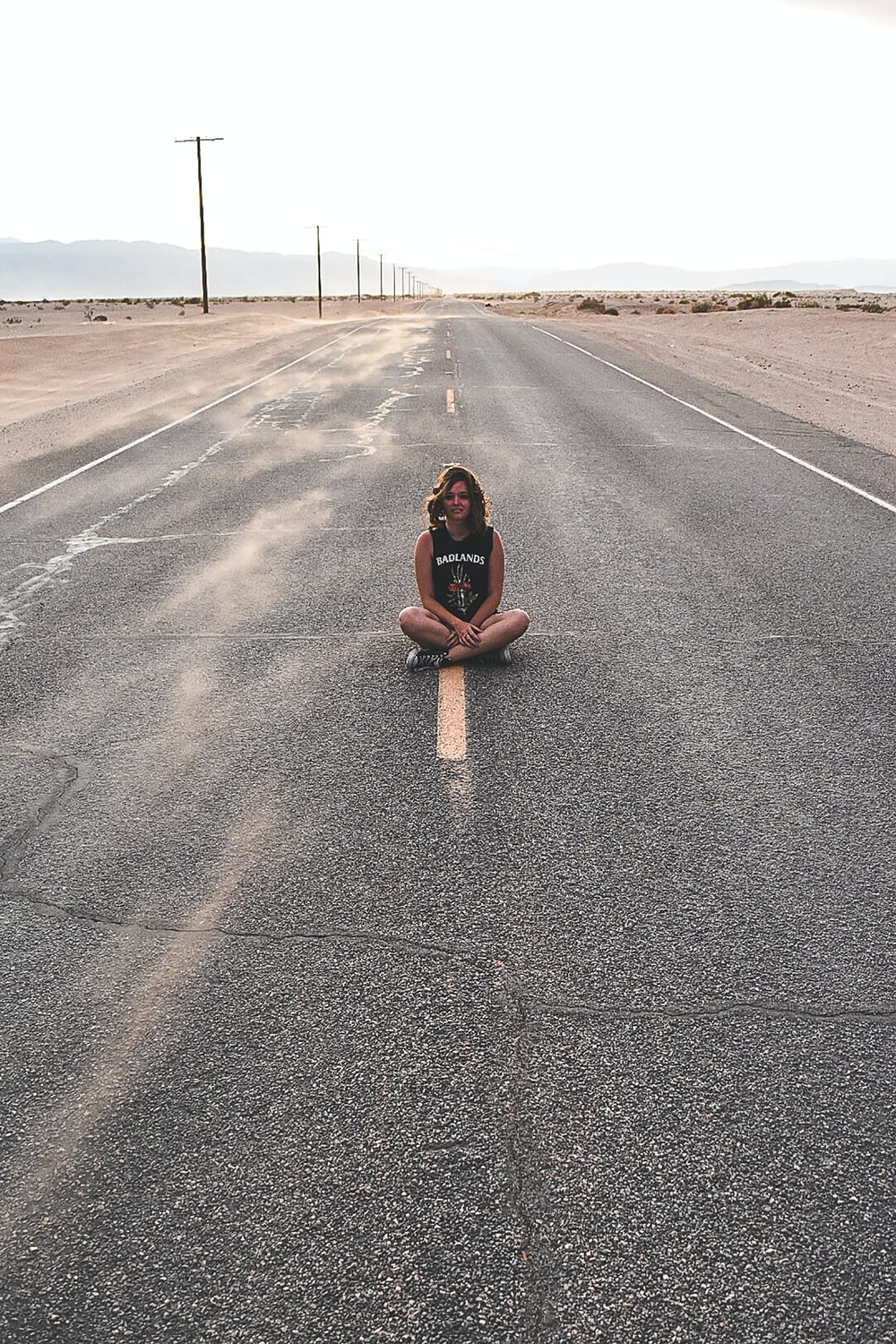 A girl sitting on yellow road line with her legs crossed.