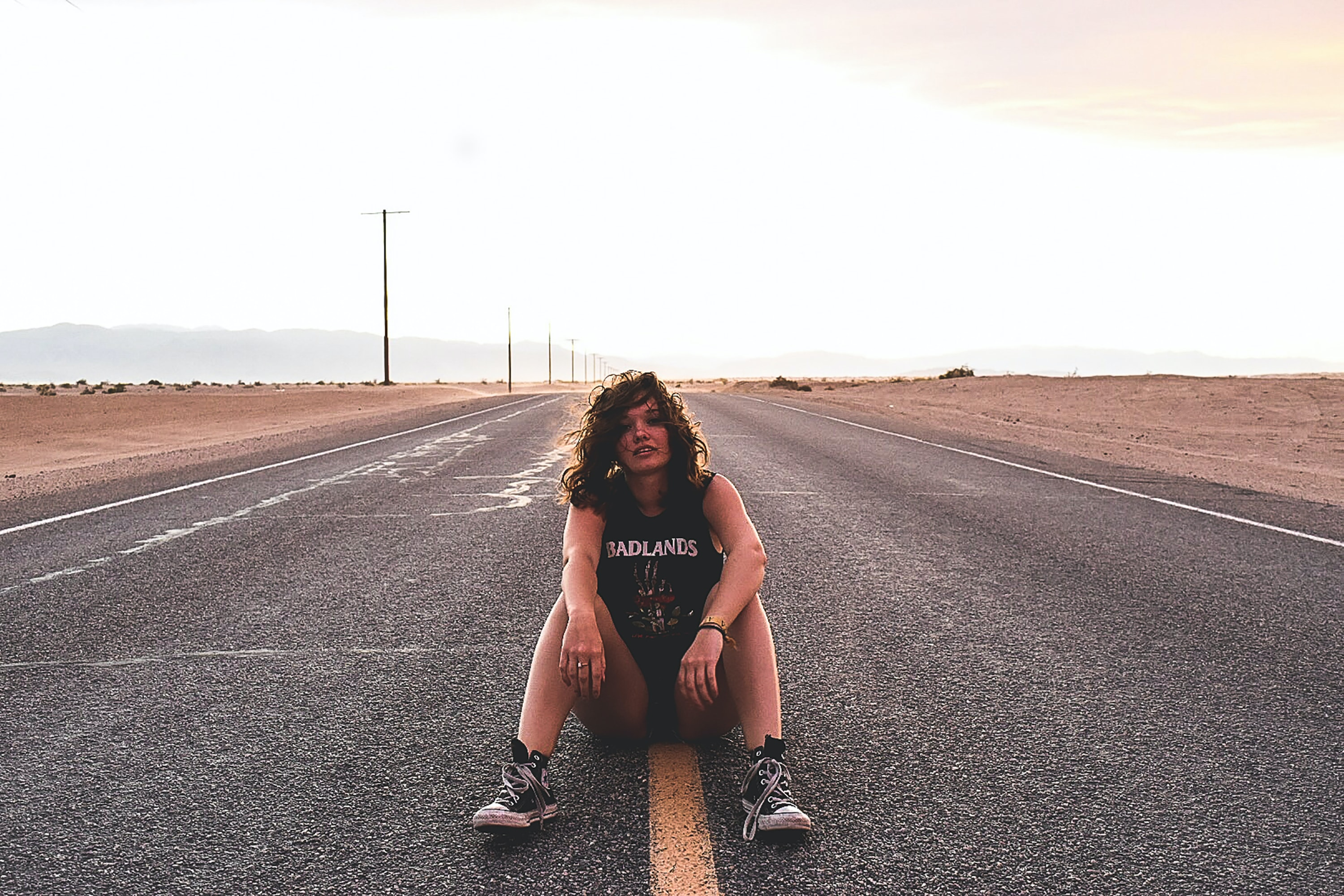 A rocker chick sitting on the yellow line in the middle of a road.