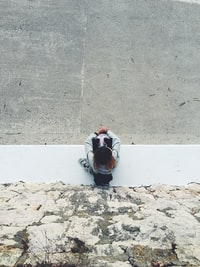 top view of person sitting near gray rock wall during daytime