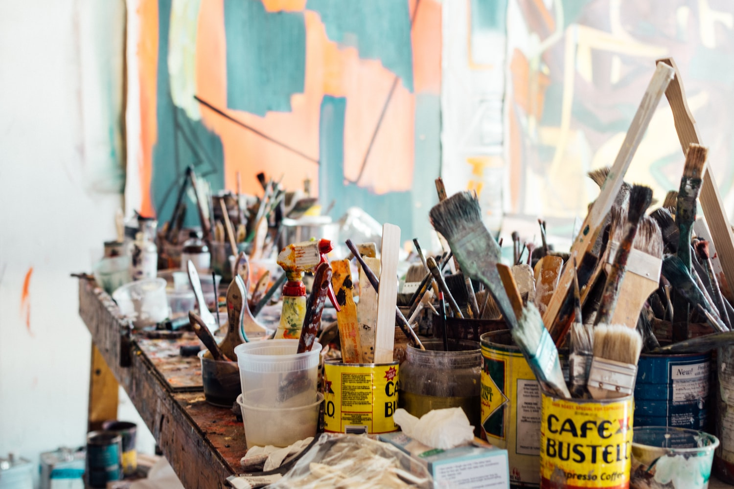 A table full of paintbrushes in different pots and cups, which you can use at the small arms building in Mississauga if you use the workshop.