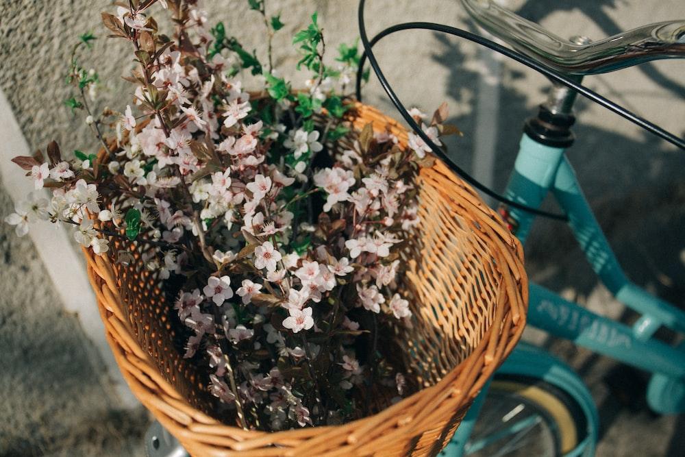 pink flowers on brown wicker basket