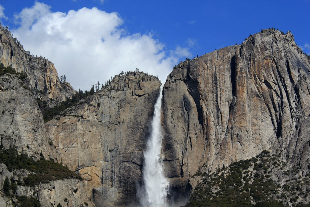 waterfalls between gray stone mountain