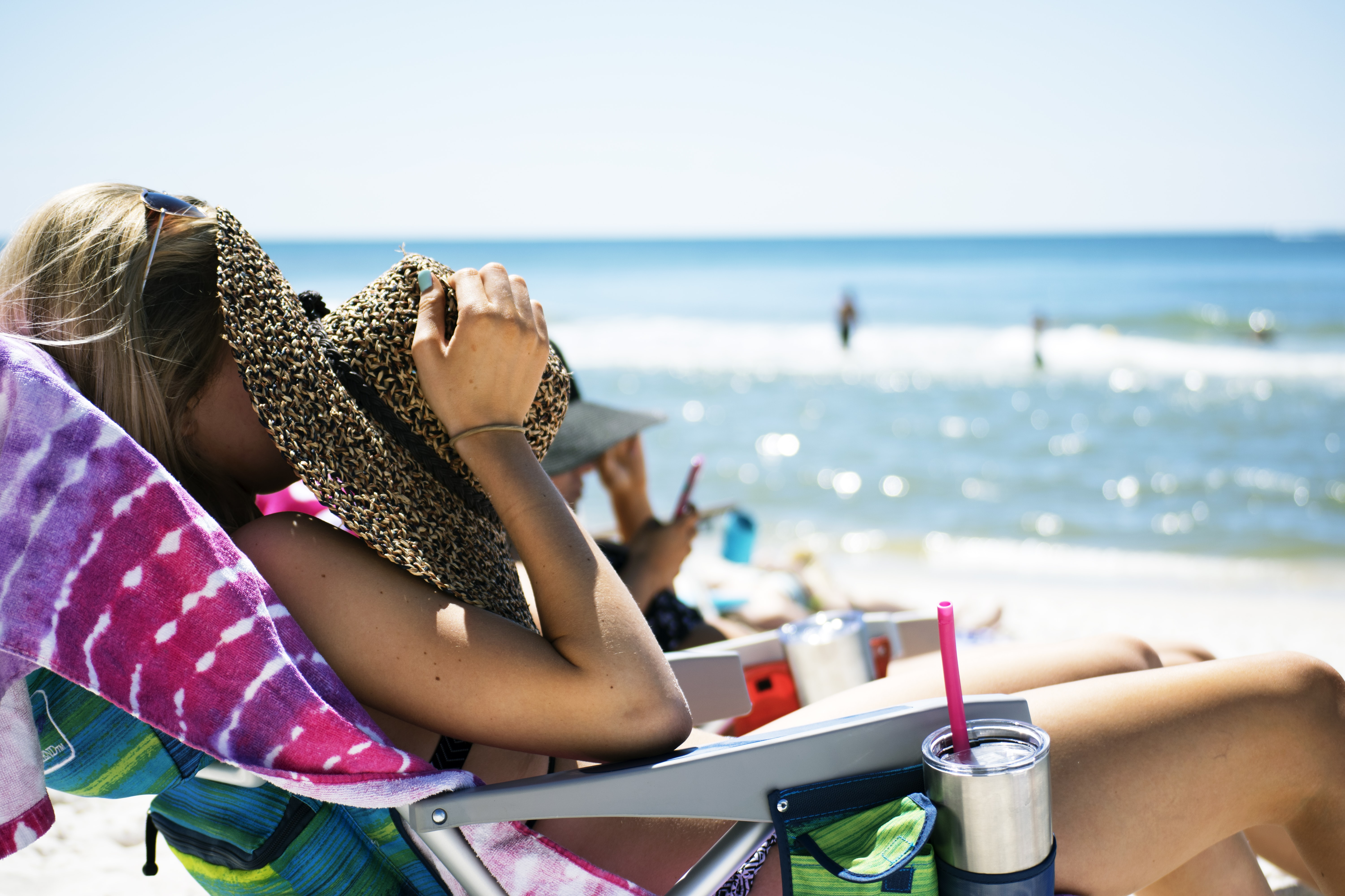 woman lying on sun lounger covering her face with straw hat near sea