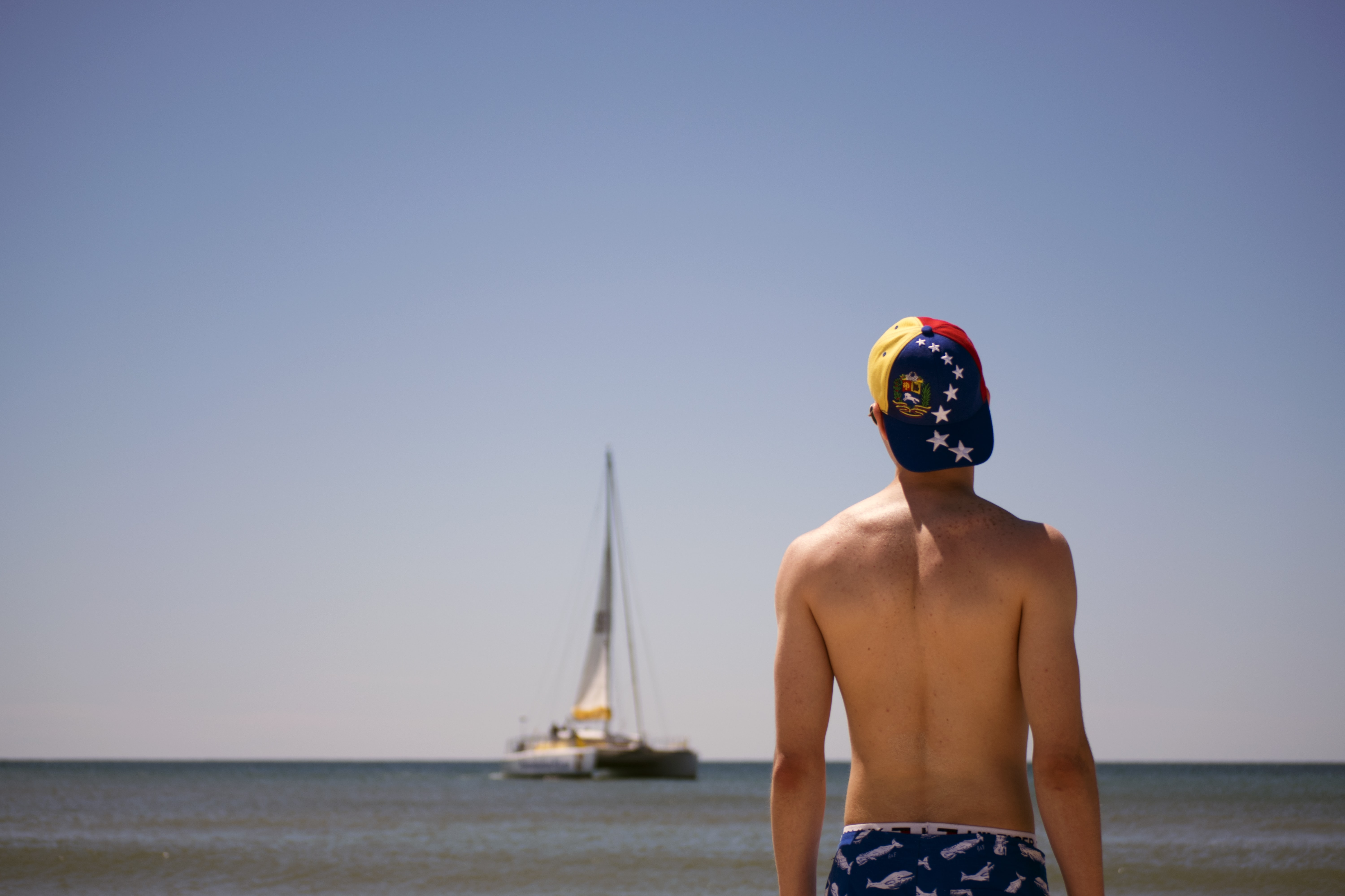 Topless man in a cap looking at the boat in the ocean at Panama City Beach