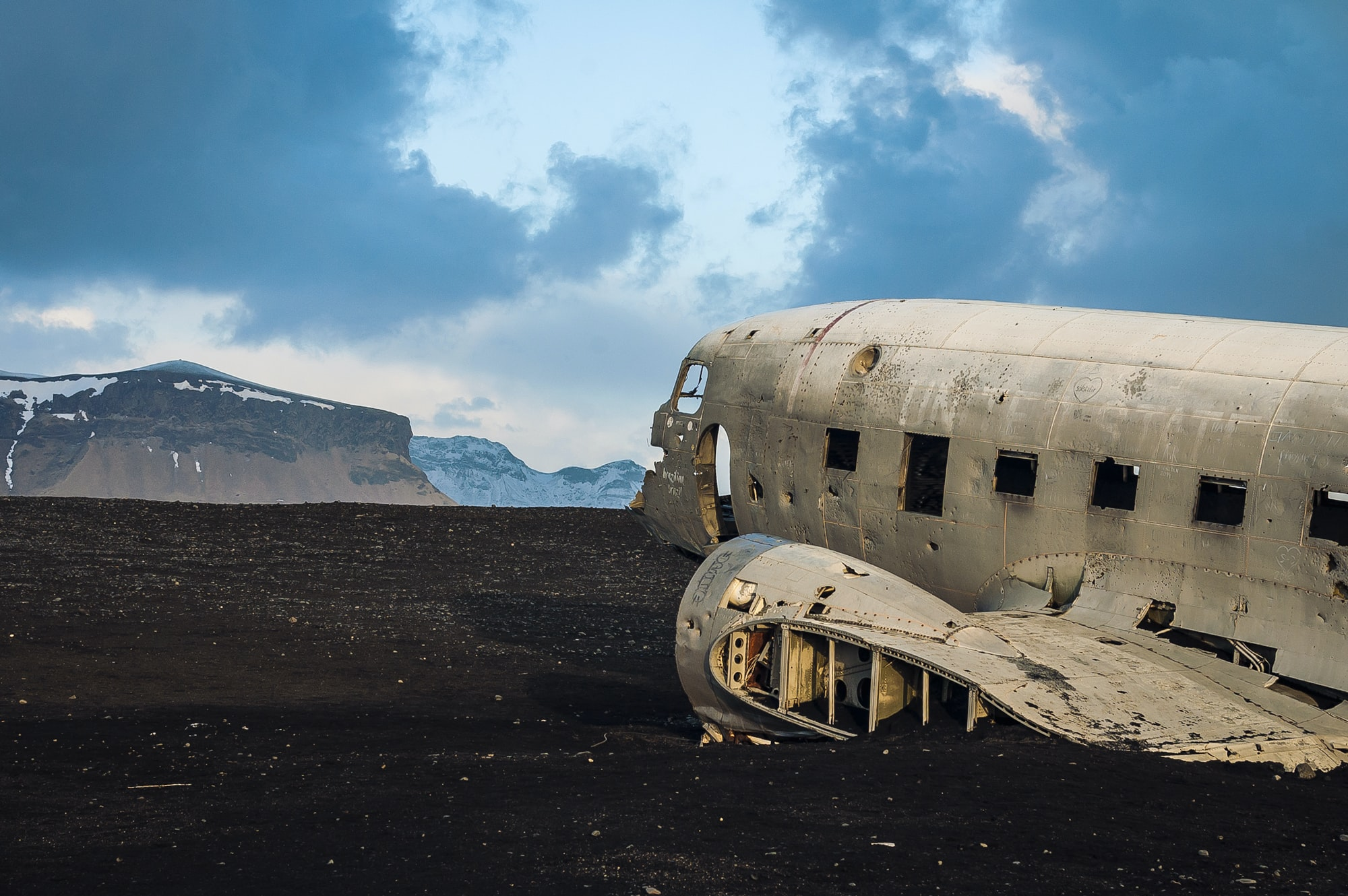 Abandoned airplane wreckage by a mountain landscape