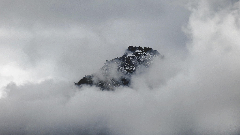 Snowy mountain summer peeks through clouds in Franz Josef Glacier