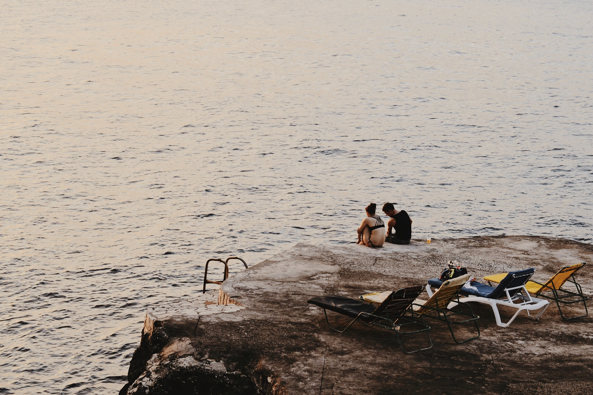 man and woman sitting on cliff beside sea and sun loungers