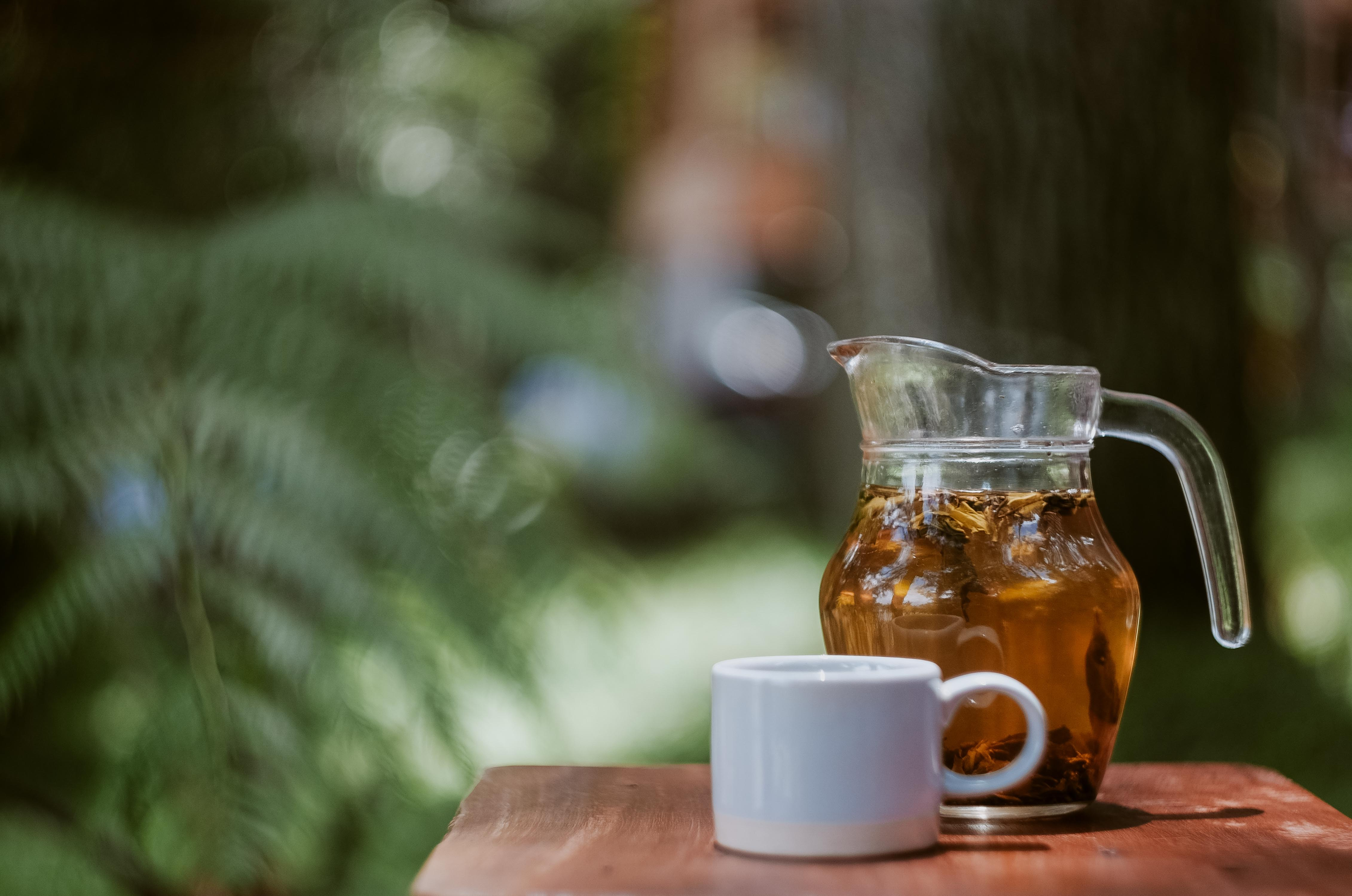 A pitcher of tea and a white mug on a wooden table