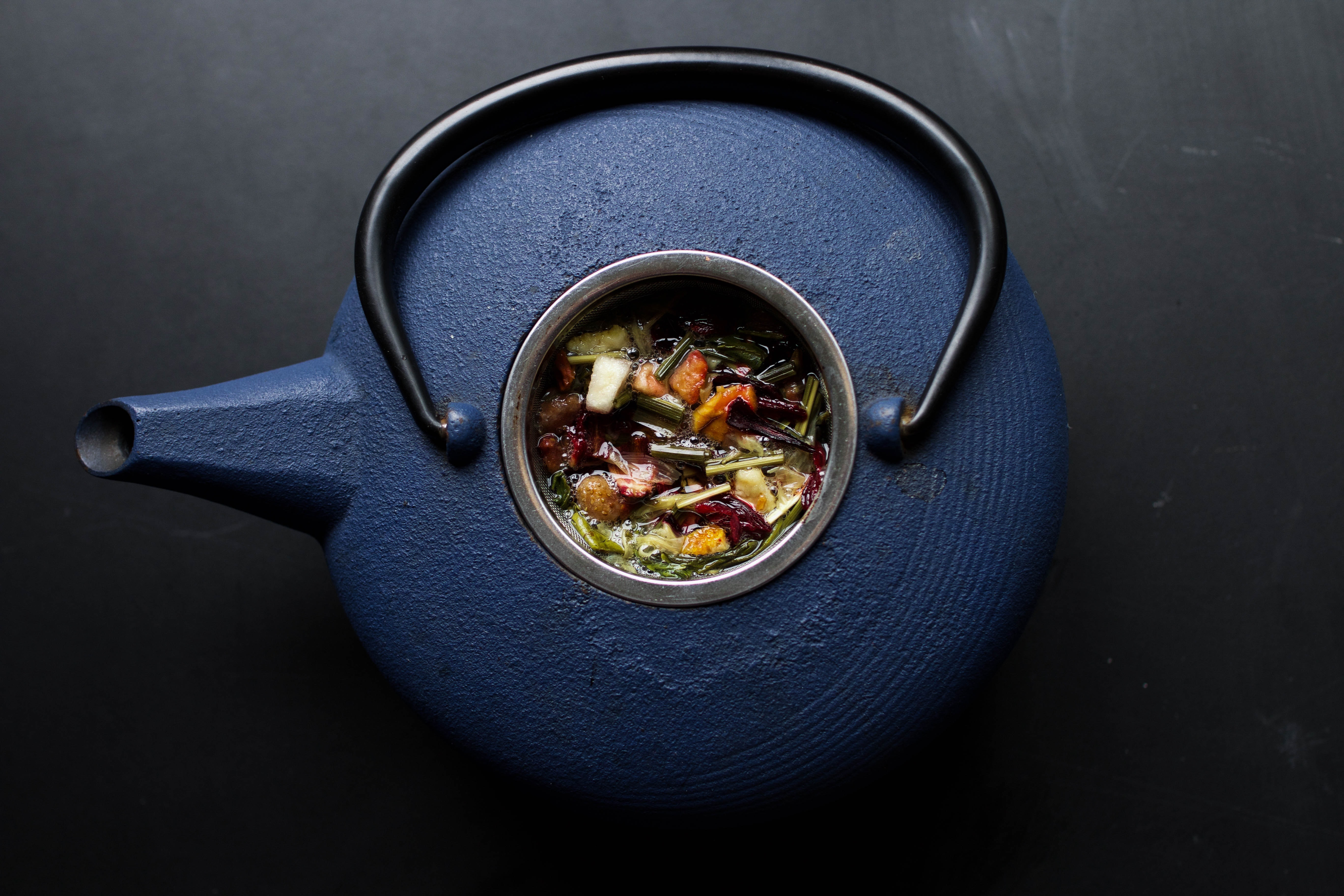 Overhead view of a blue kettle teapot filled with herbs at Laguna Beach