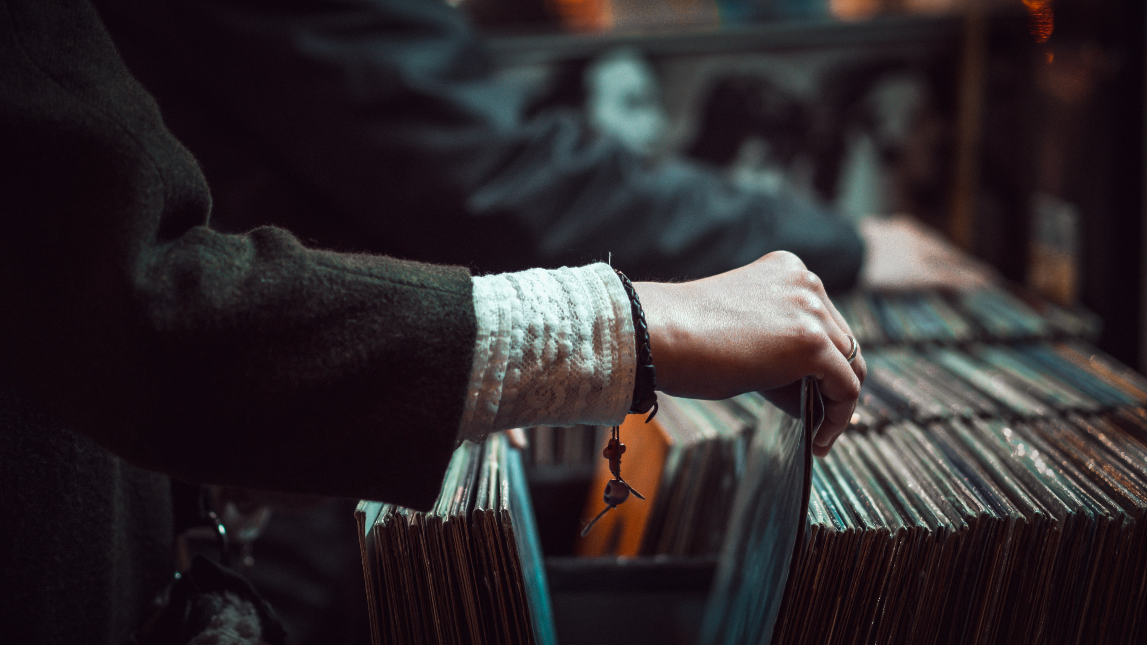 A close-up of the hand of a person browsing vinyl records at a store