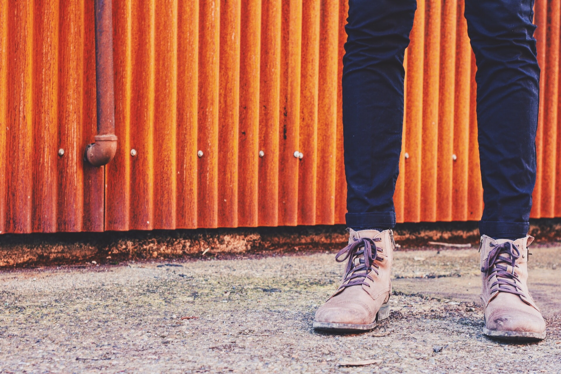 A down low shot of a man's shoes and skinny jeans with a rustic setting
