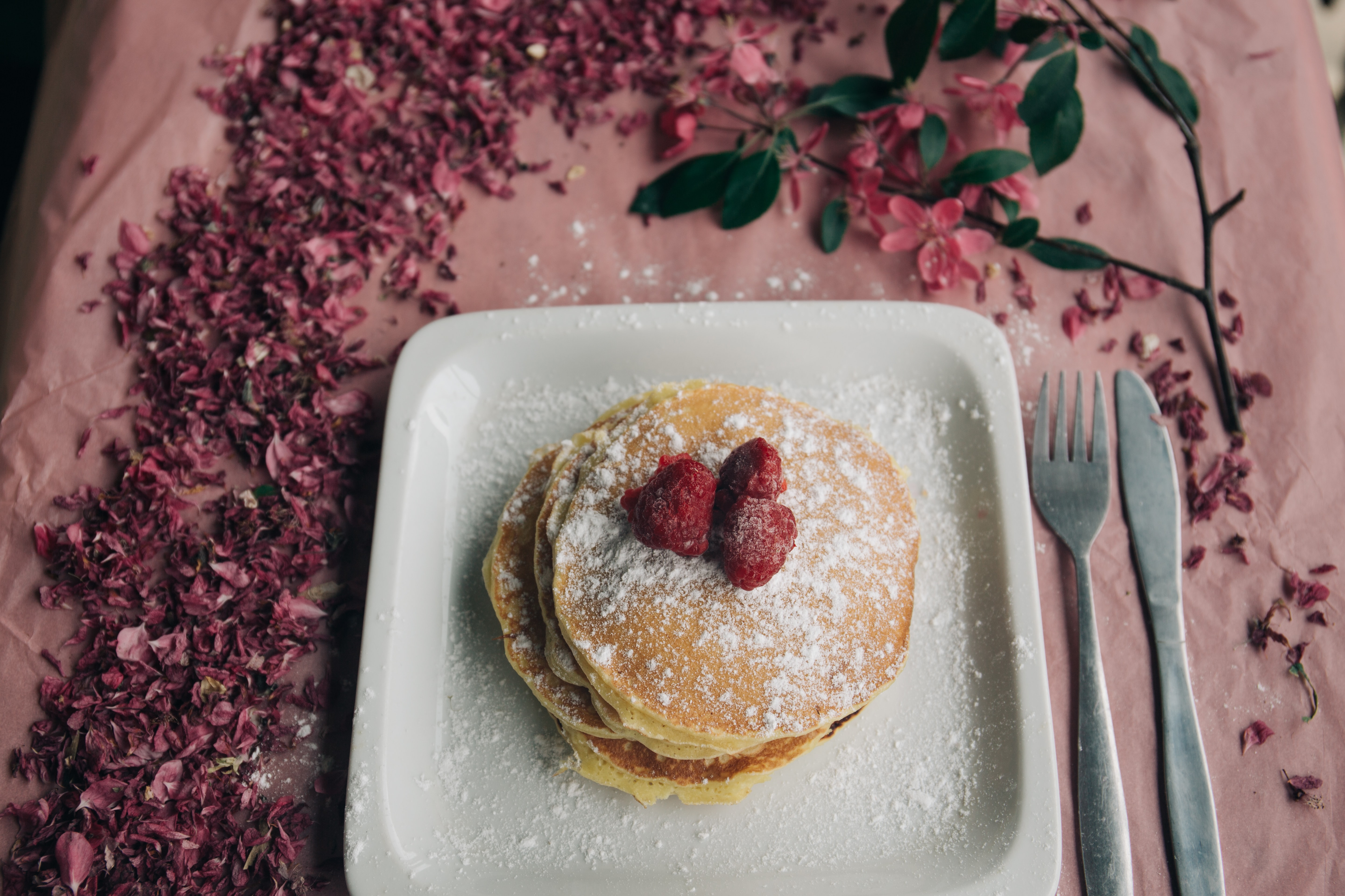 Delicious looking pancakes covered in berries and powdered sugar on a plate that is sitting on a table with flowers on it