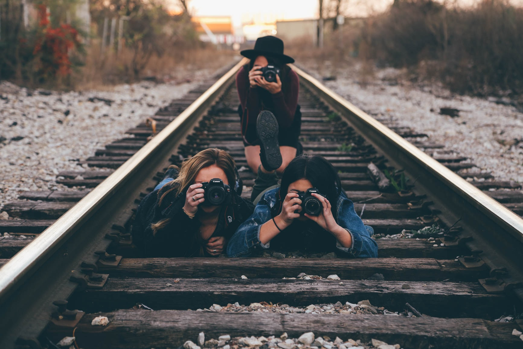 Three young women with cameras taking a photo while on a railroad track