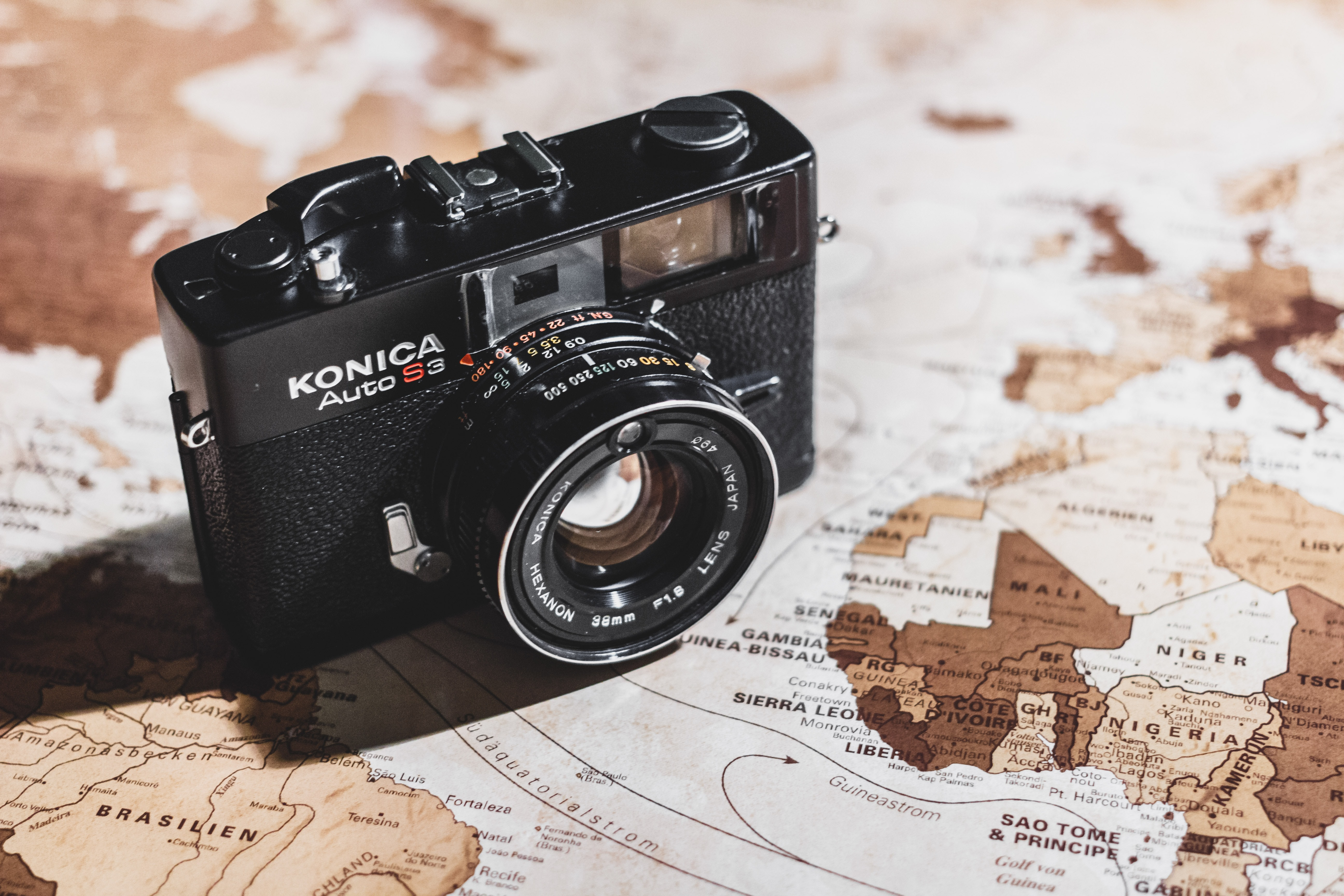 A close-up of a Konica Auto S3 camera on an old world map