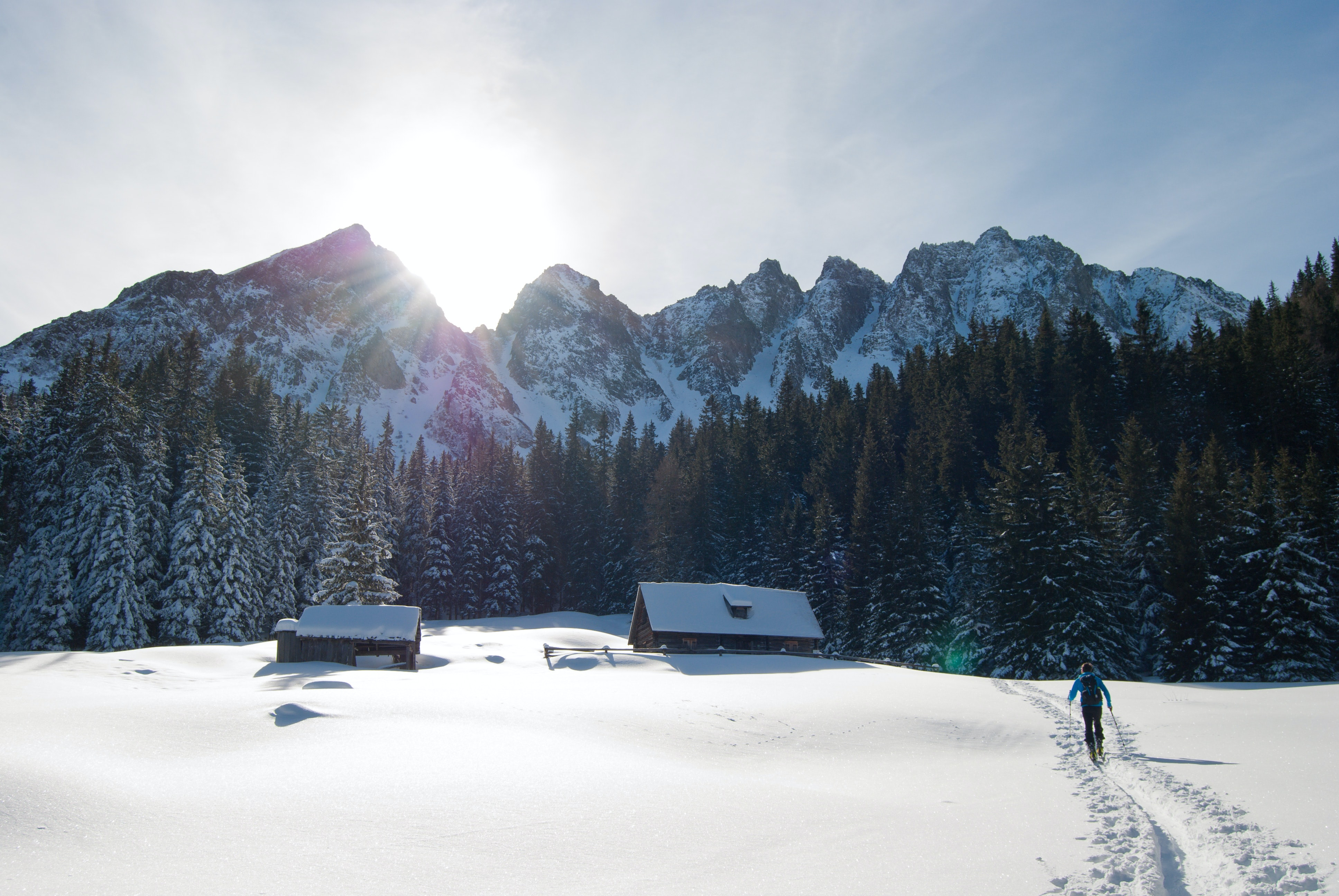 A person walking in the snow to a house near sunny the mountain peaks