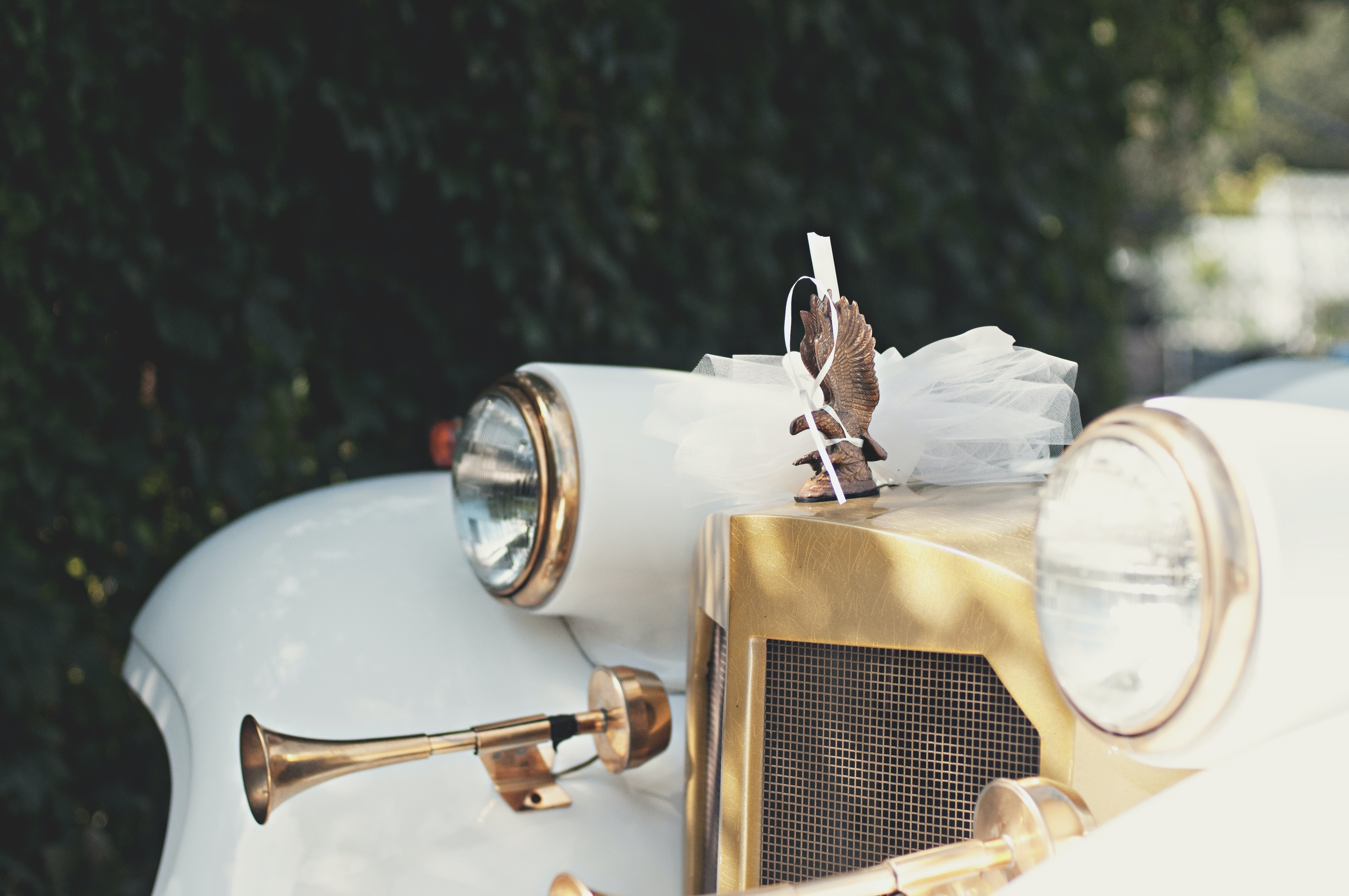 Close up of white gold retro Rolls Royce car on sunny wedding day