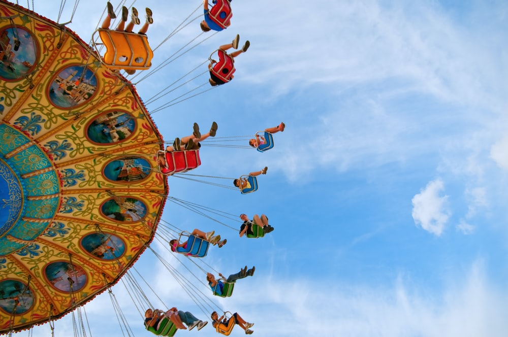 people riding carnival ride under blue skies