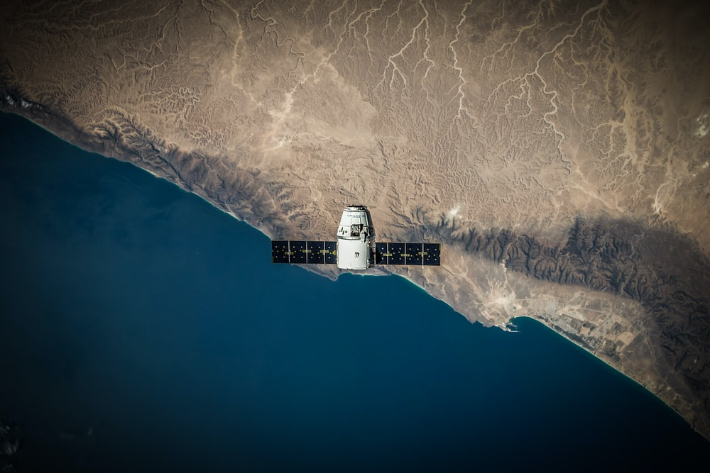 A space satellite hovering above the coastline