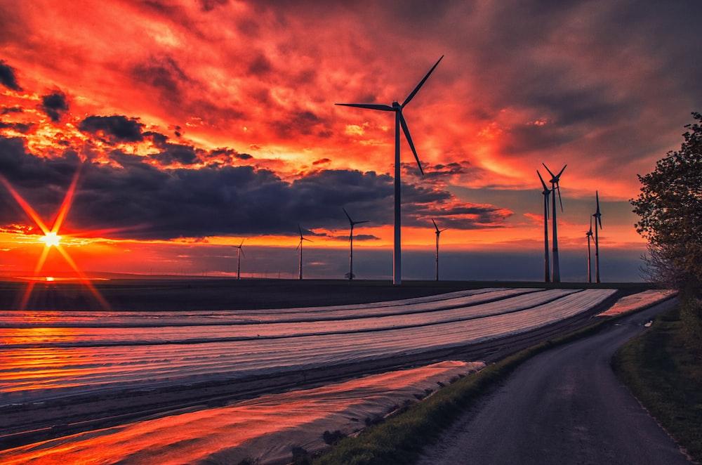 wind turbines on gray asphalt road during sunset