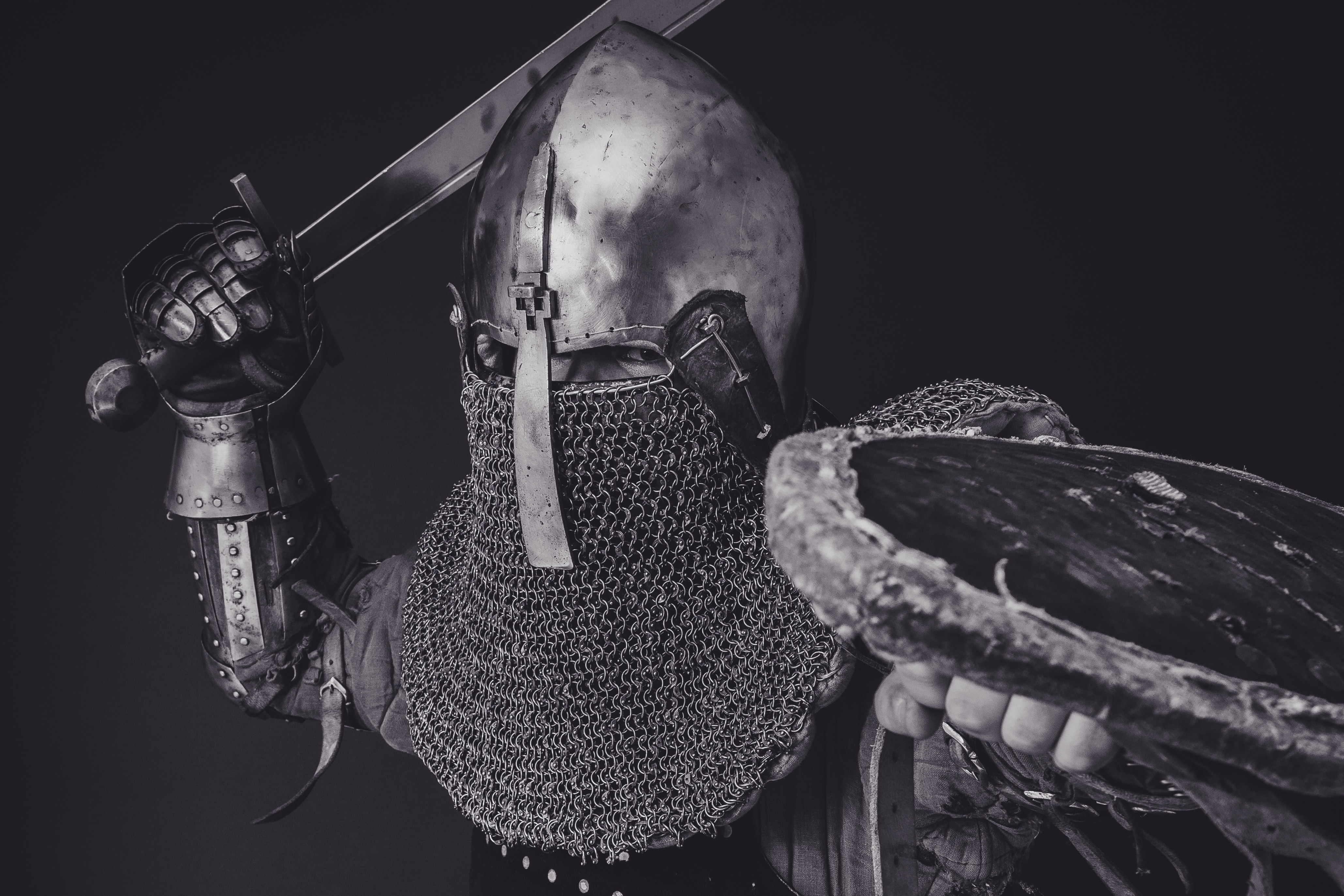black and white portrait of a man in Medieval armor, getting ready to swing a sword.
