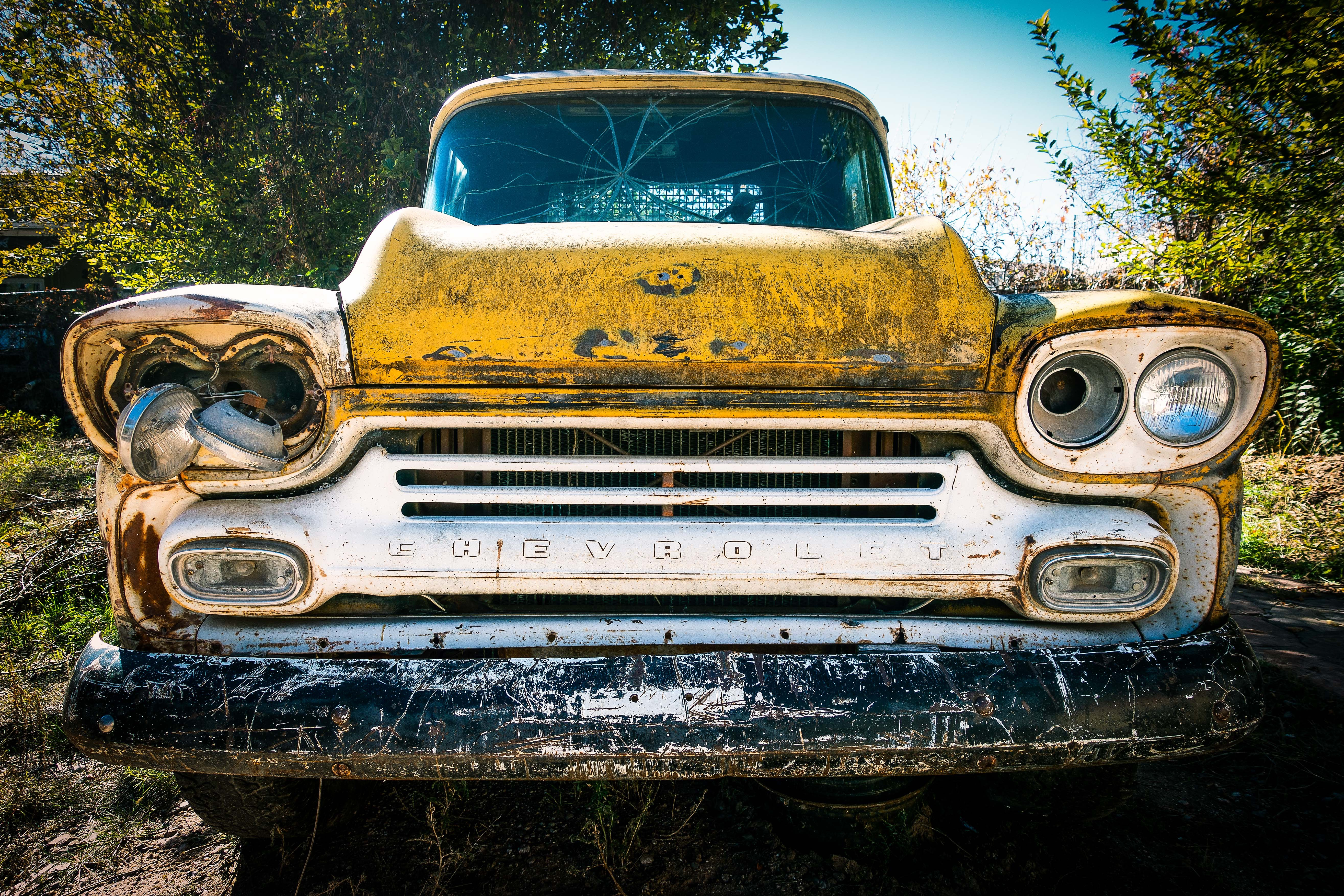 Close up of rusty, retro Chevy with broken grille, windshield and headlights in New Mexico