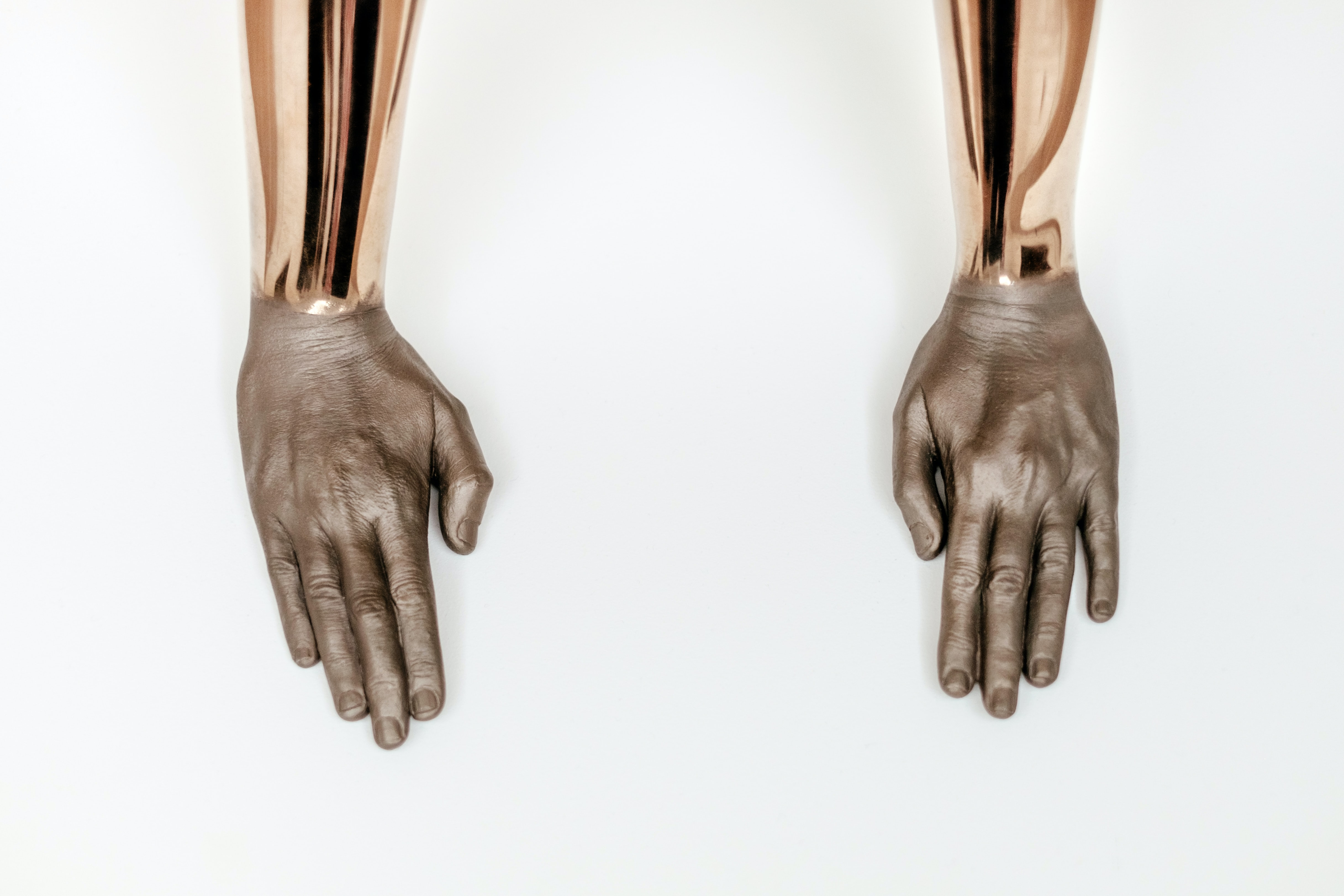 Sculpture of golden arms and human hands resting on a white surface in Fundação Serralves