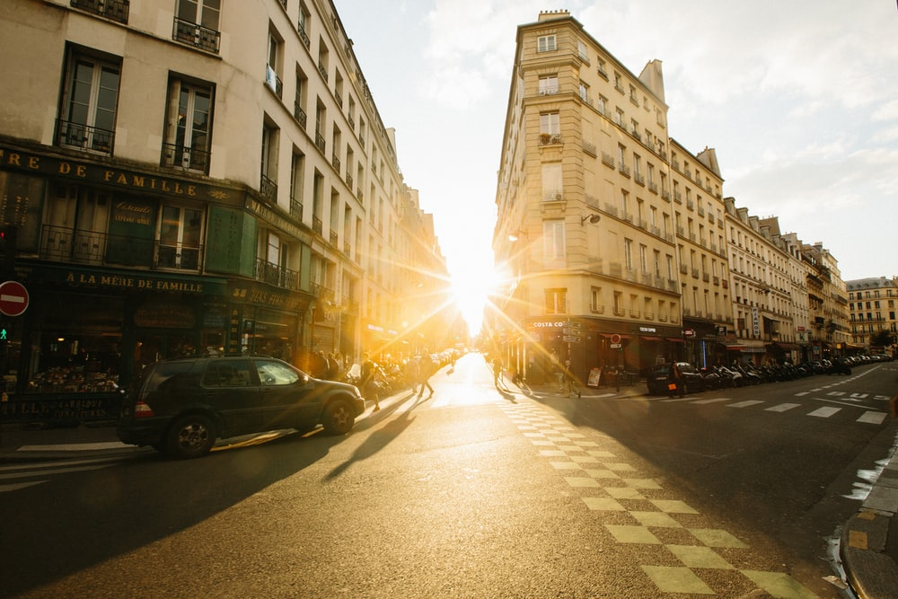 Sunset on a street in Paris with a green vehicle, pedestrian crossing and traditional Parisien buildings