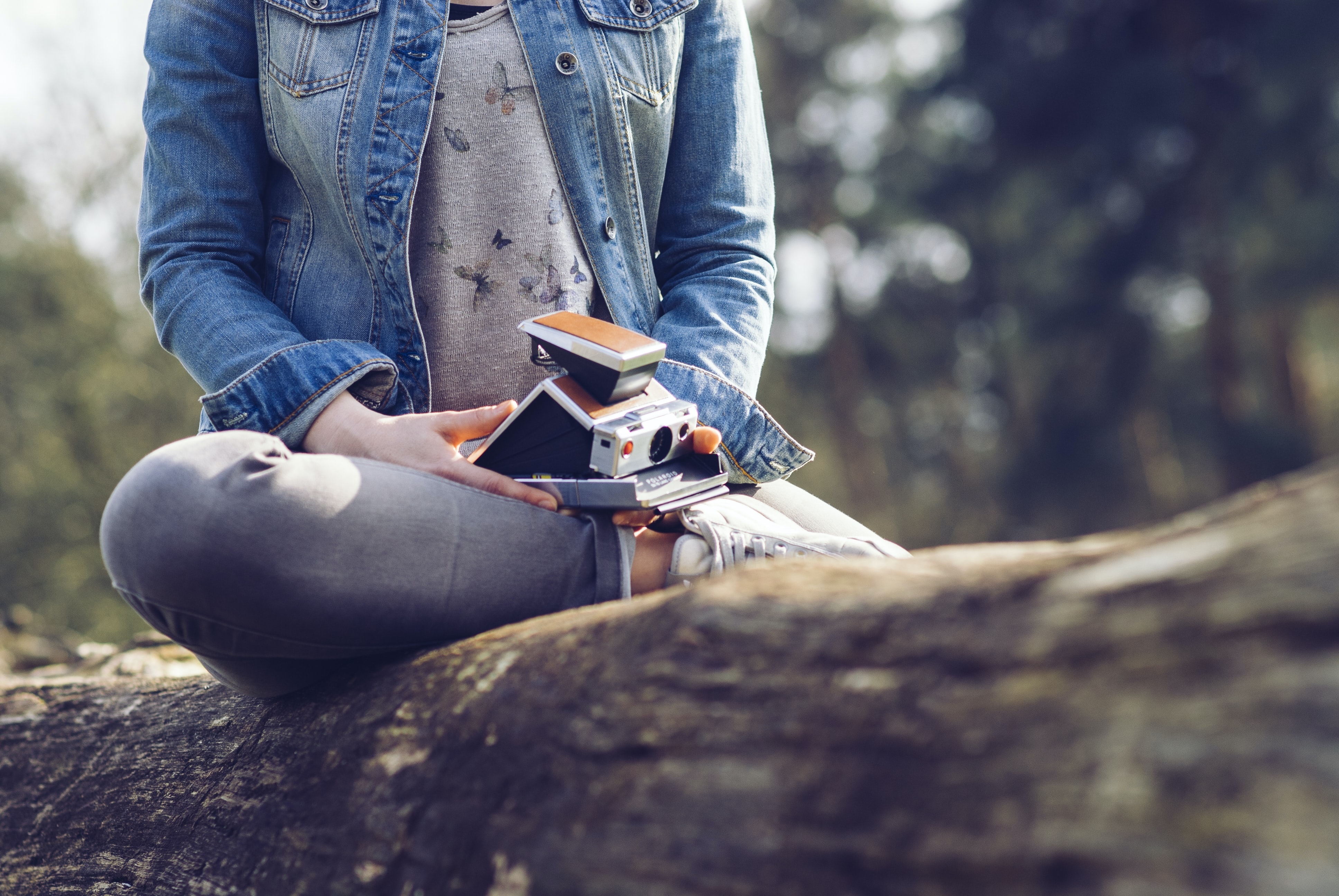 woman sitting on log holding camera and book