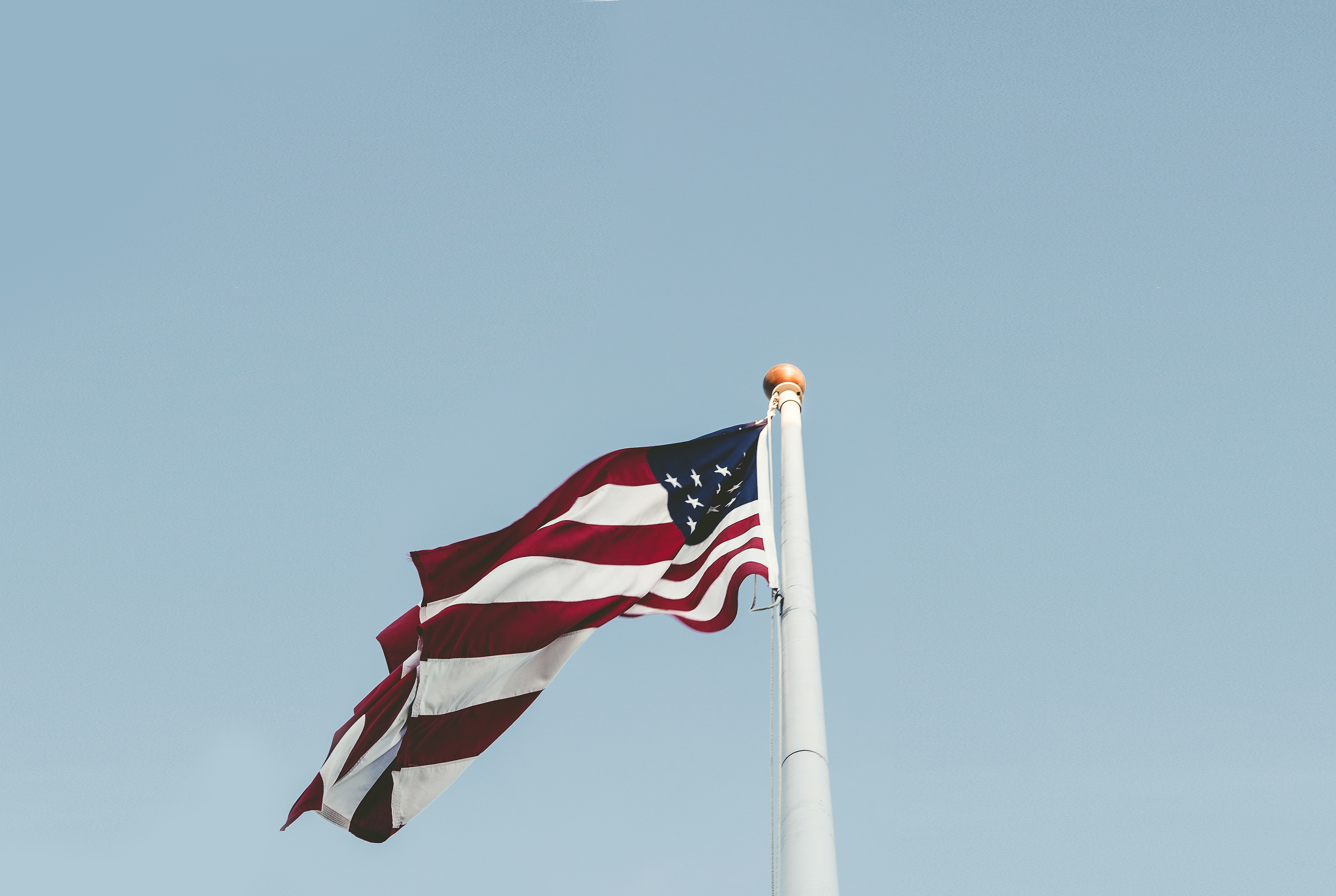 American flag flying in the wind atop a flagpole