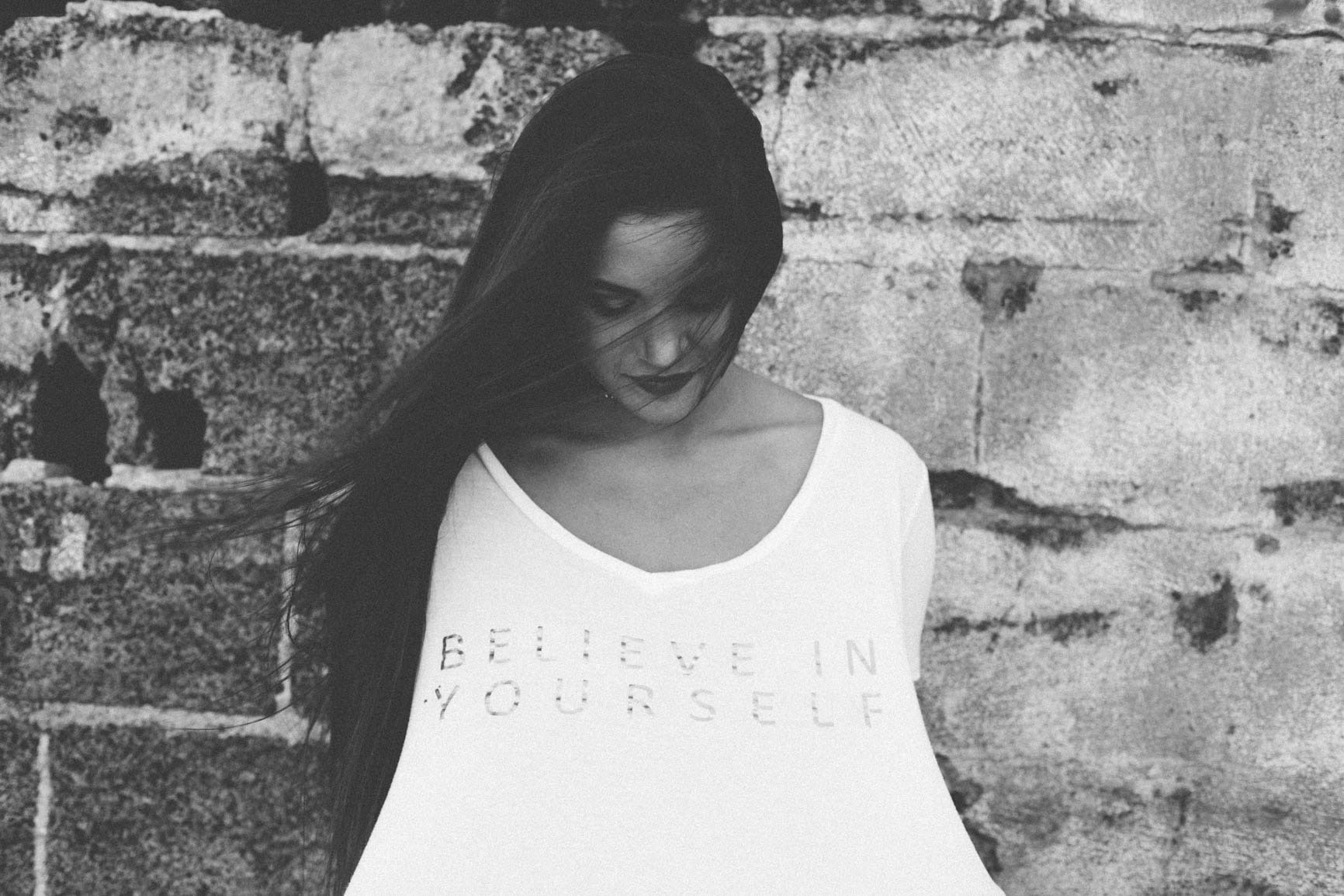 "A woman looking down at her shirt which reads ""Believe in yourself."""