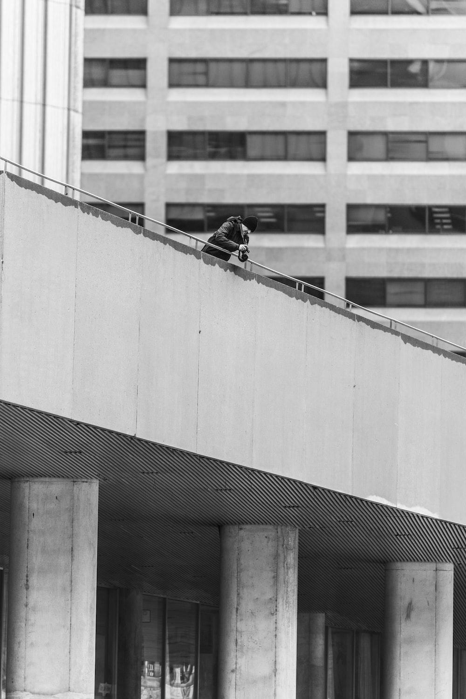 grayscaled photo of man leaning against bridge railing