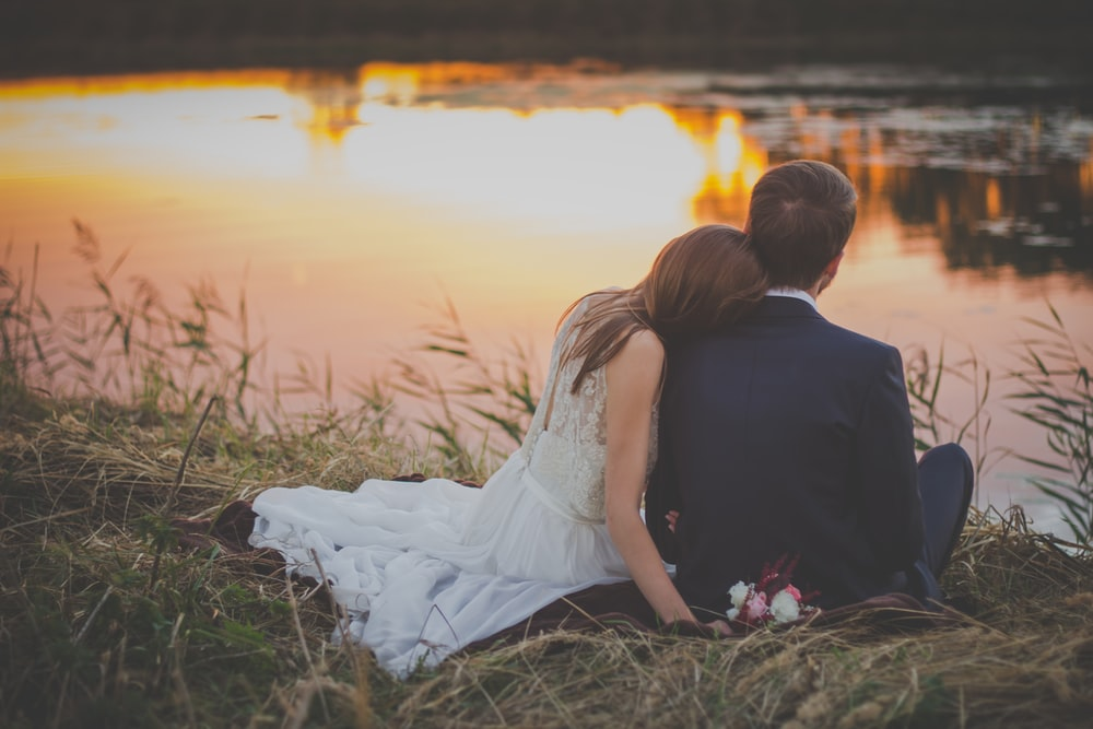 Bride rests head on groom while looking at a pond during sunset