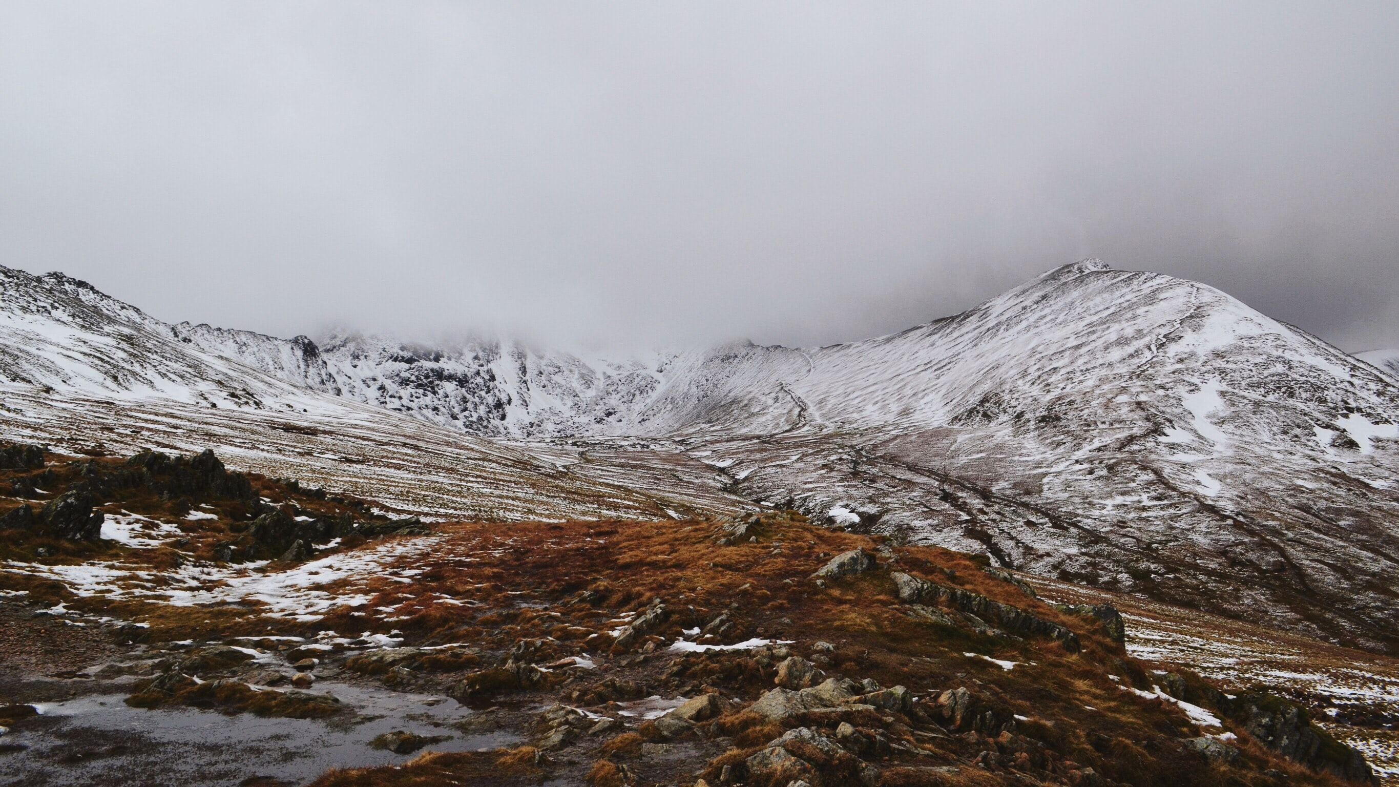 Clouds descend on a valley that is dusted with snow.