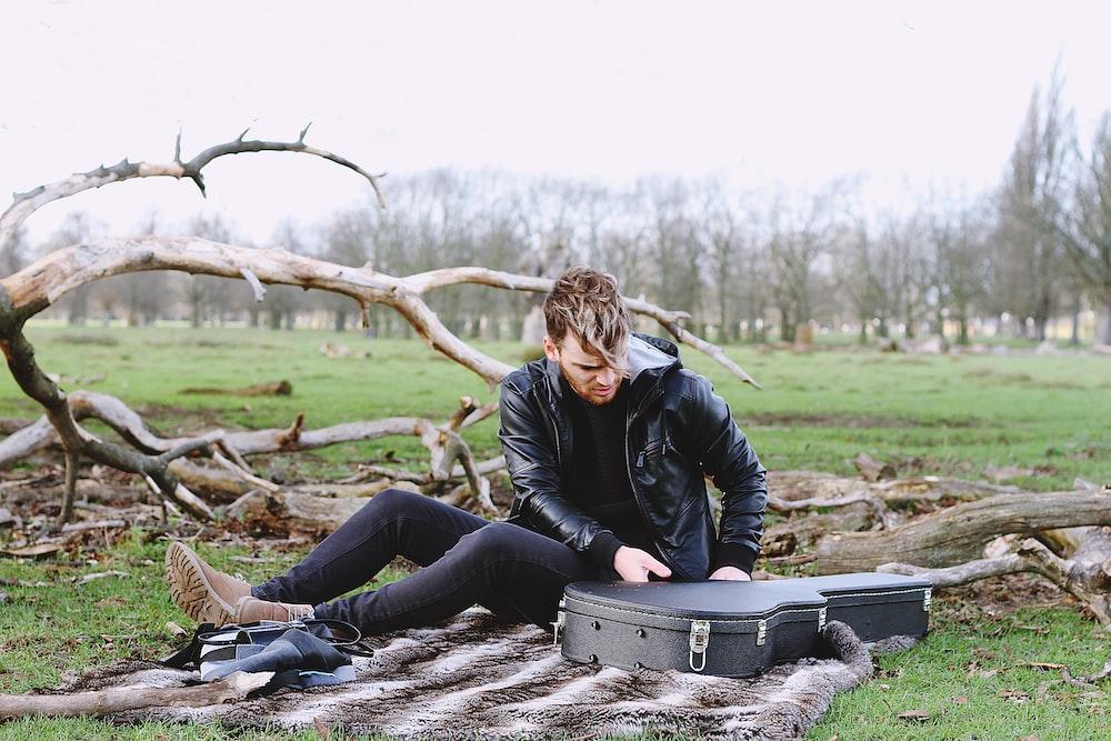 man siting holding guitar case