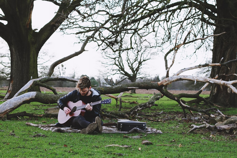 men holding a guitar near trees during daytime