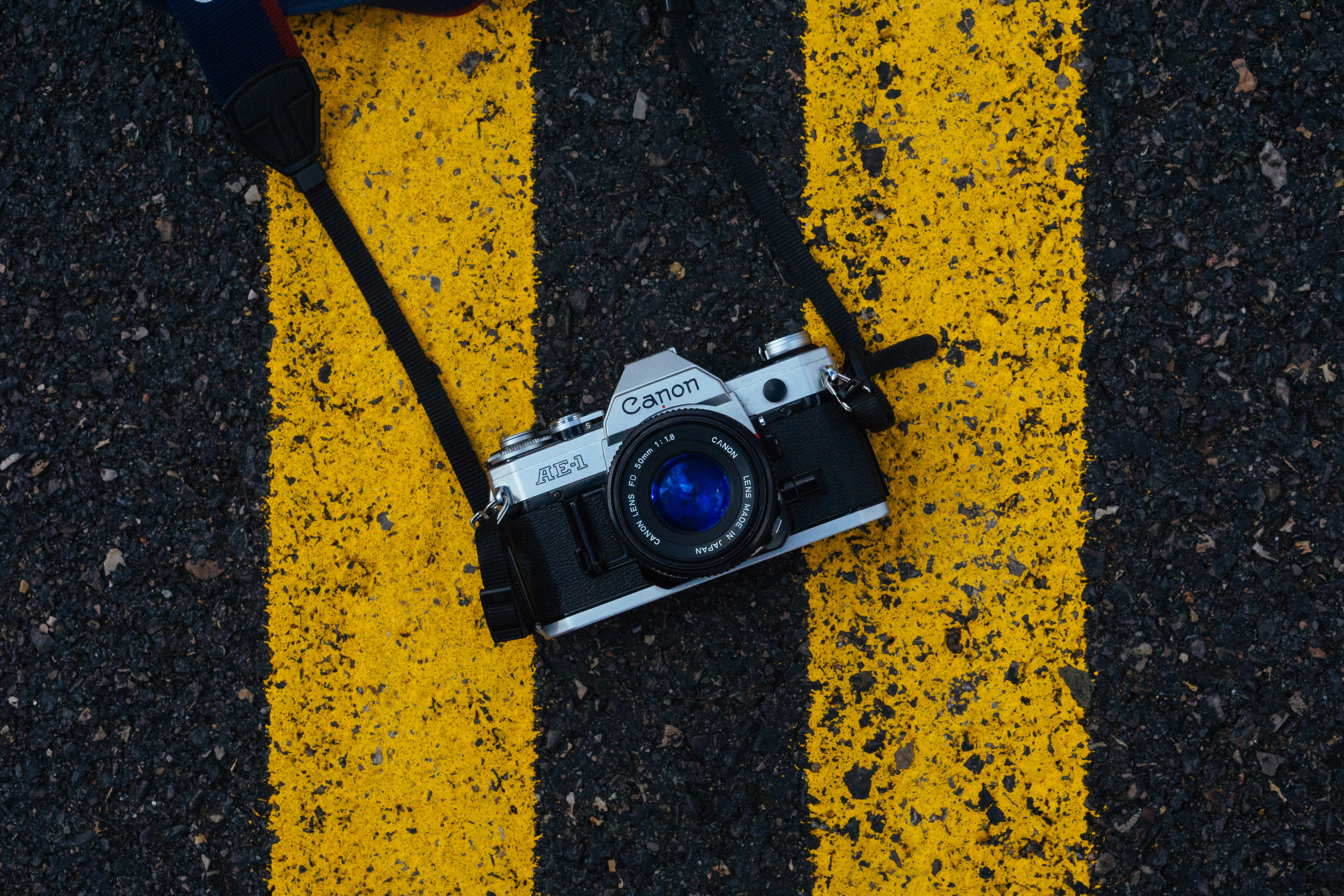 gray and black Canon SLR camera on road
