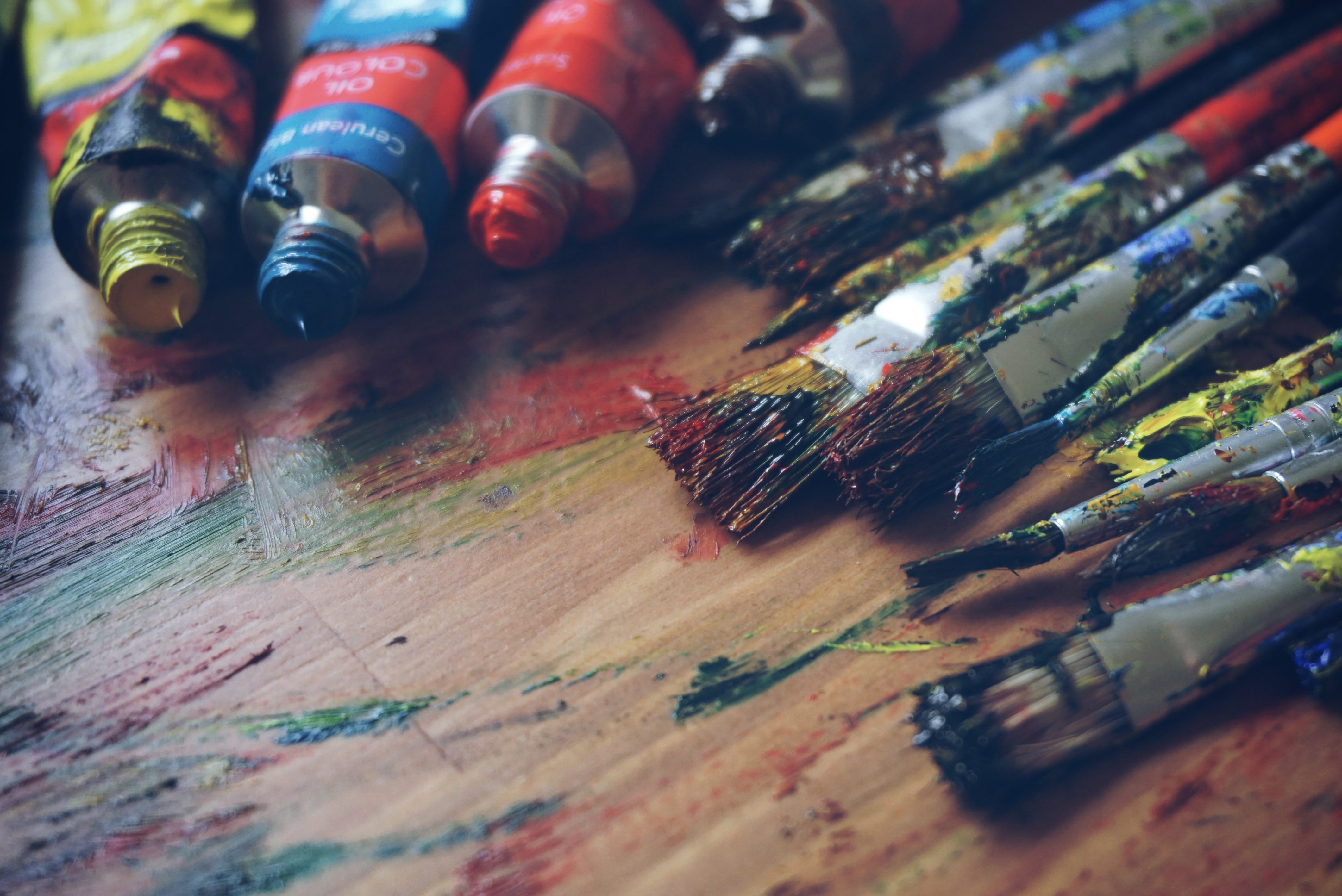 Close up of paint tubes, brushes and bristles with smeared painted on table, Ljubljana