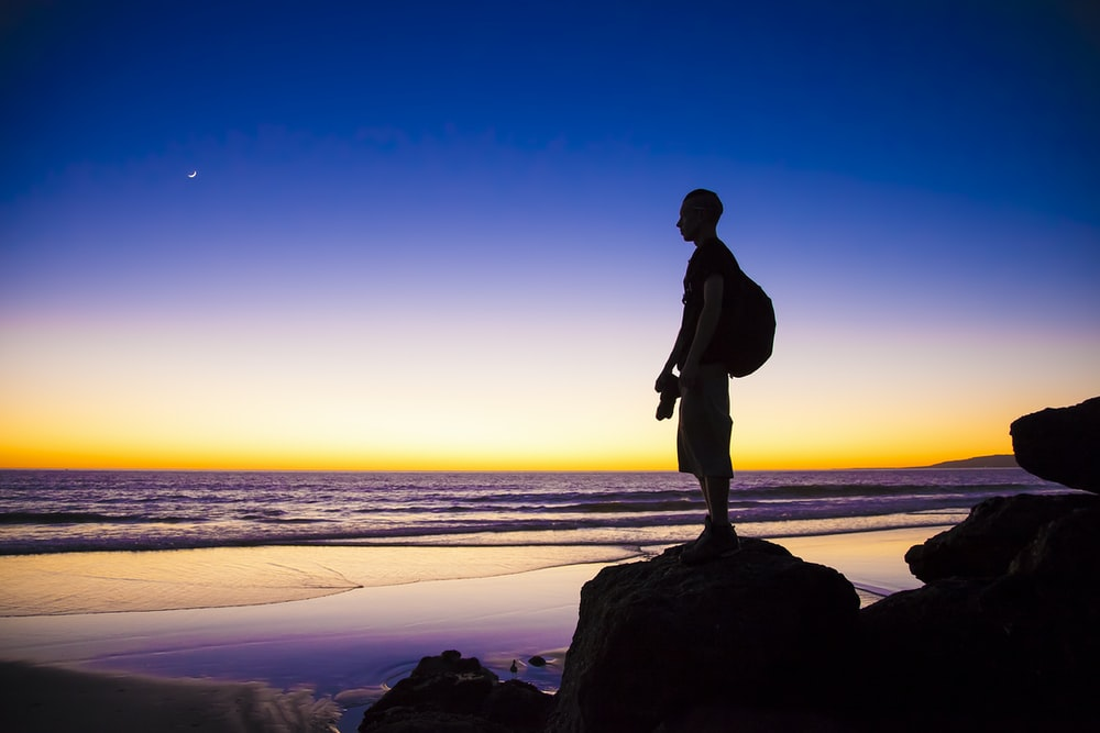 silhouette of man standing on cliff
