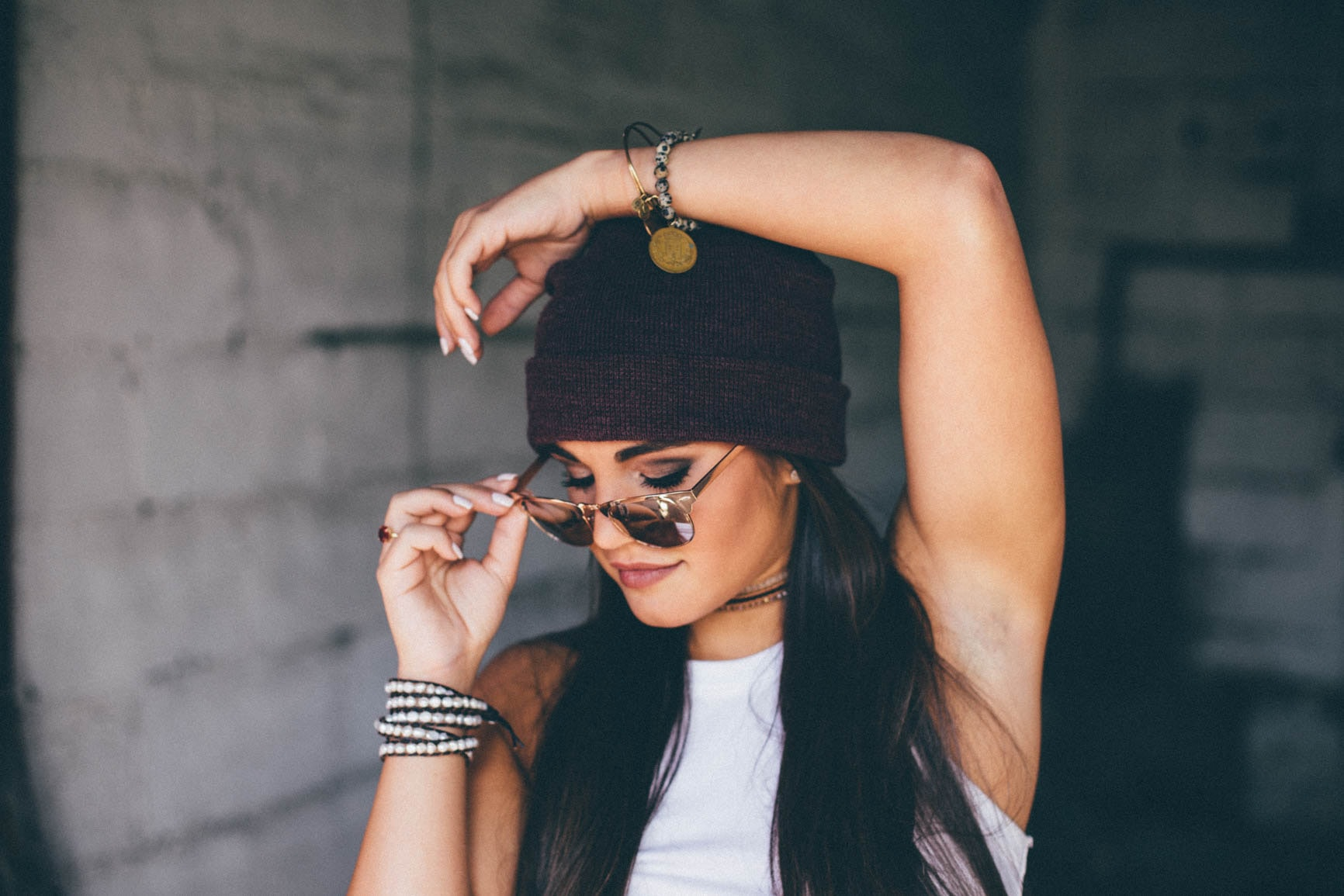 A young woman in a beanie holding her sunglasses with one hand