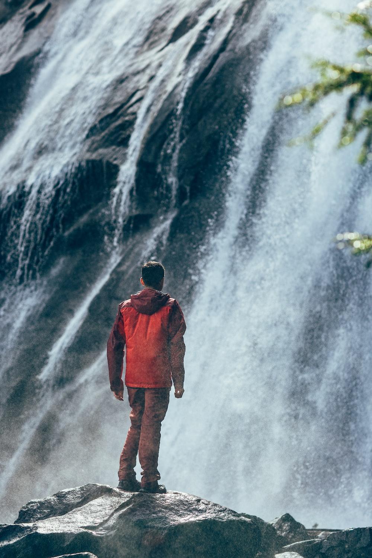 man standing on rock facing waterfall
