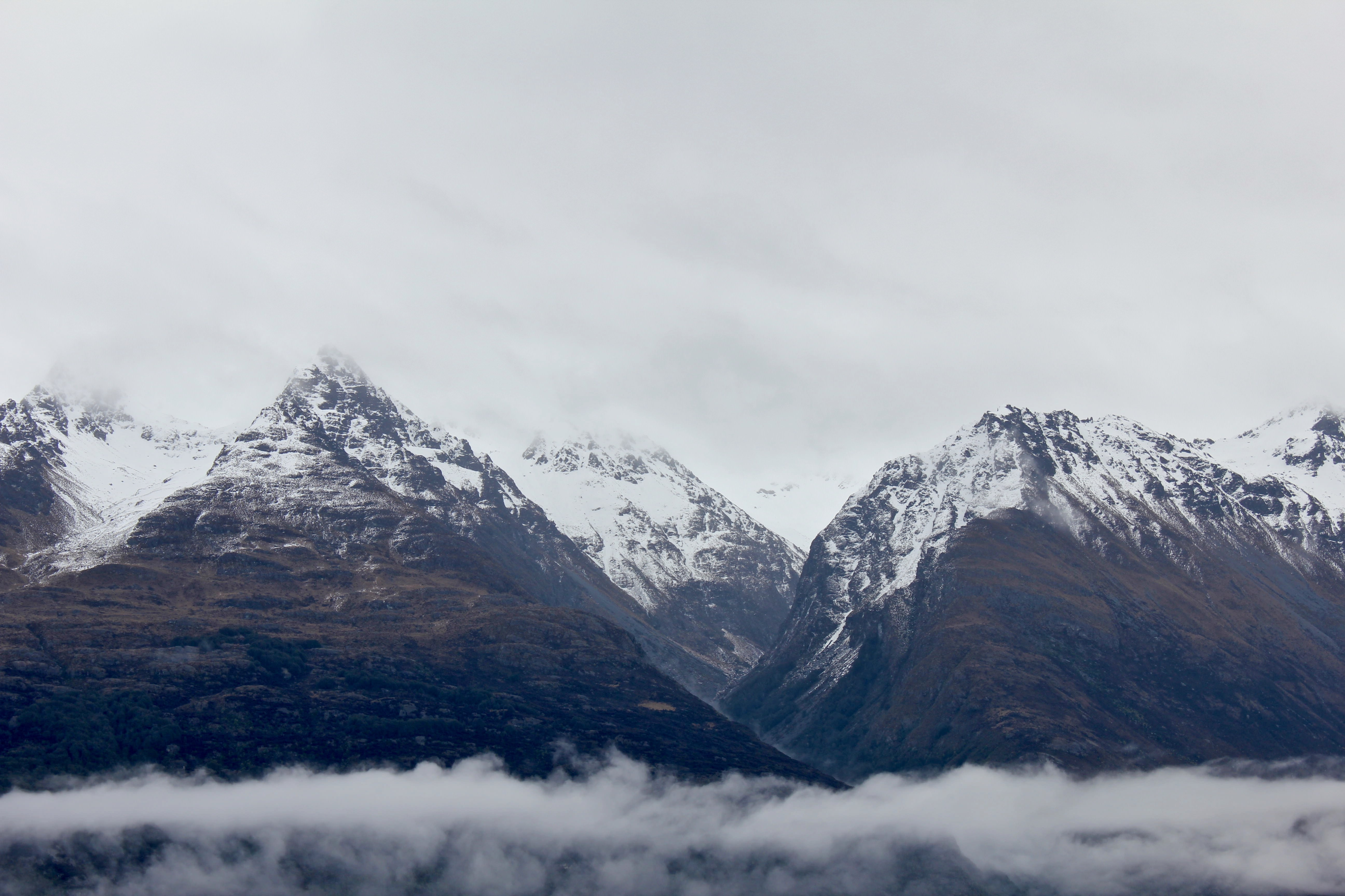 Snow covered mountain peaks surrounded by clouds in Queenstown.