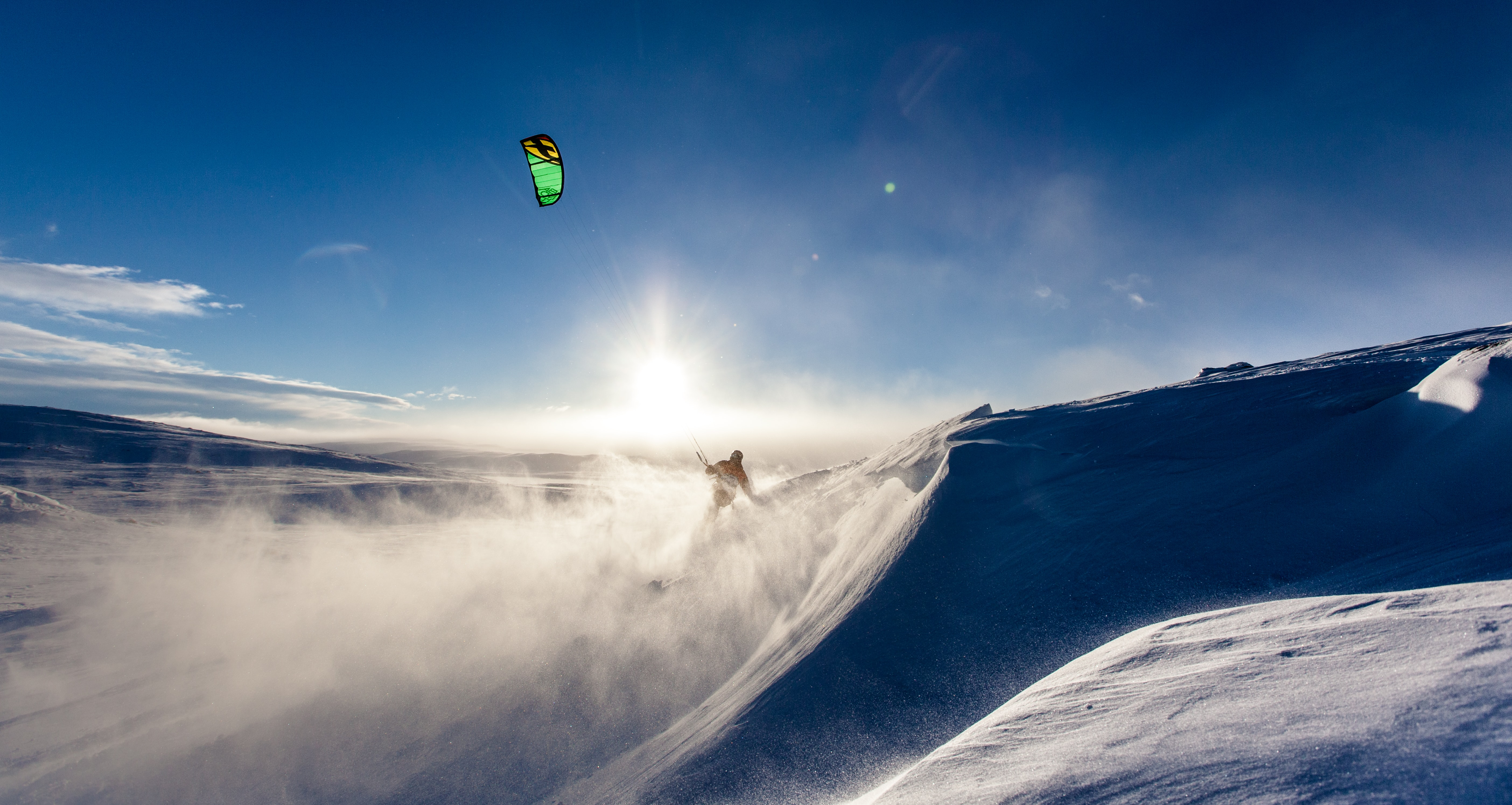 A silhouette of kiteboarder kicking up snow on a mountain