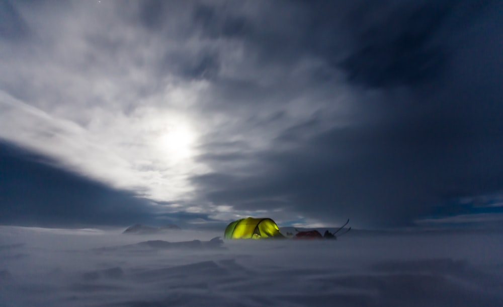 green tent in the middle of snow field