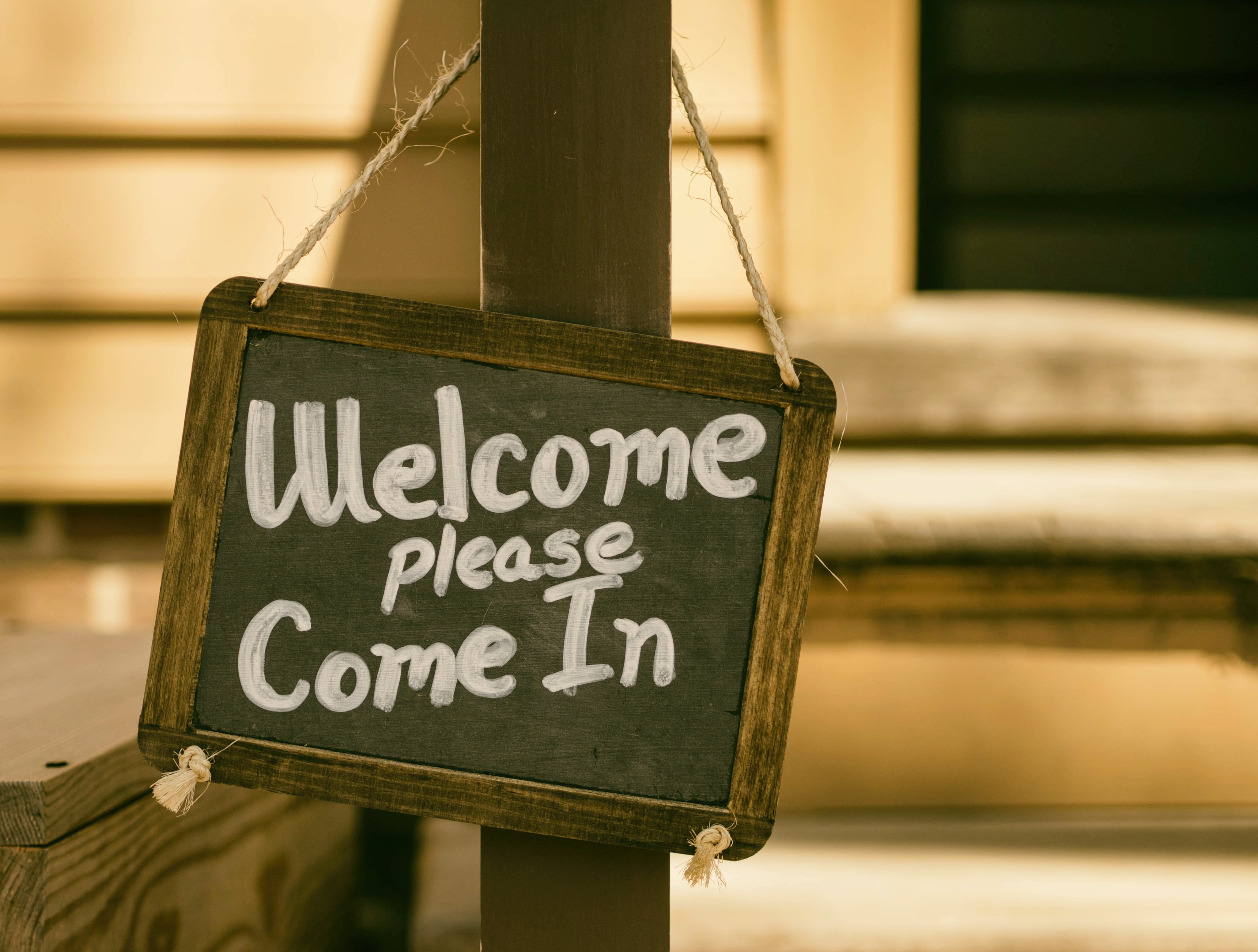 """A chalkboard sign hanging from a pole, which reads """"Welcome please come in."""""""