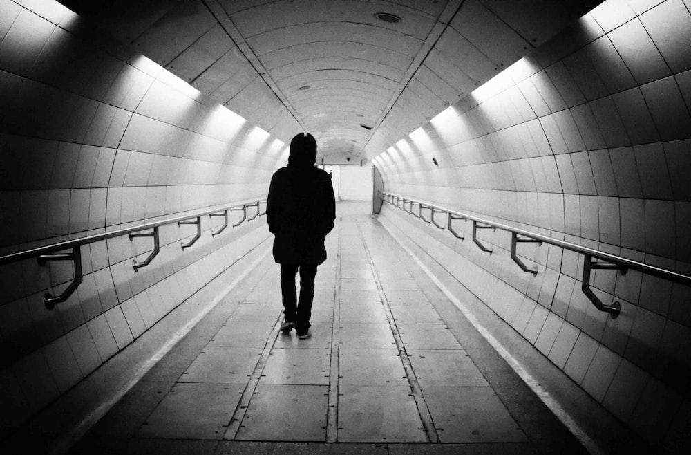 woman in black coat walking on tunnel